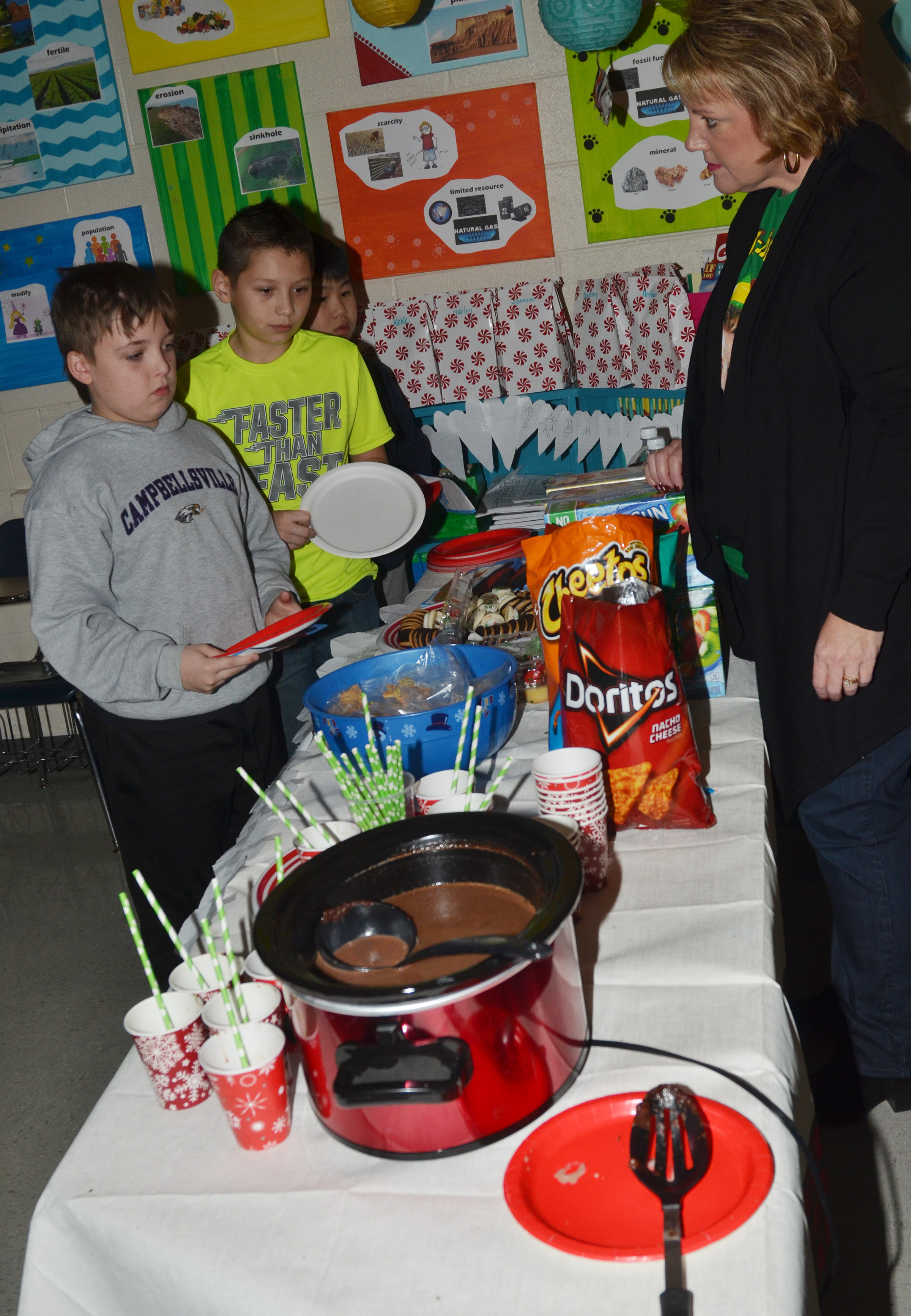 CMS fourth-grade teacher Kaye Agathen treats her students with special goodies during her class's Christmas party.