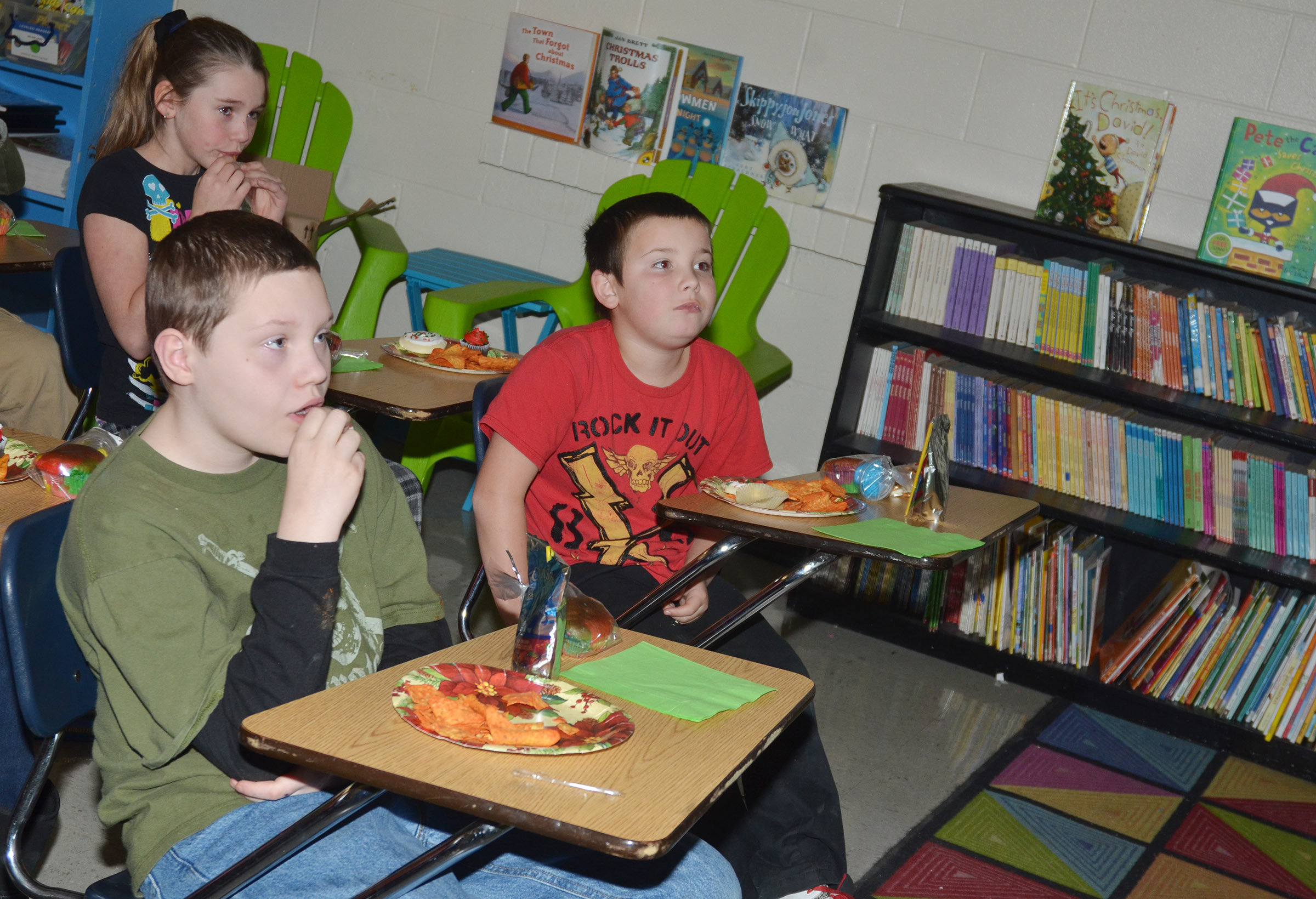 CMS fourth-graders Ethan Cox, at left, and Christopher Orberson enjoy snacks while watching a Christmas movie.