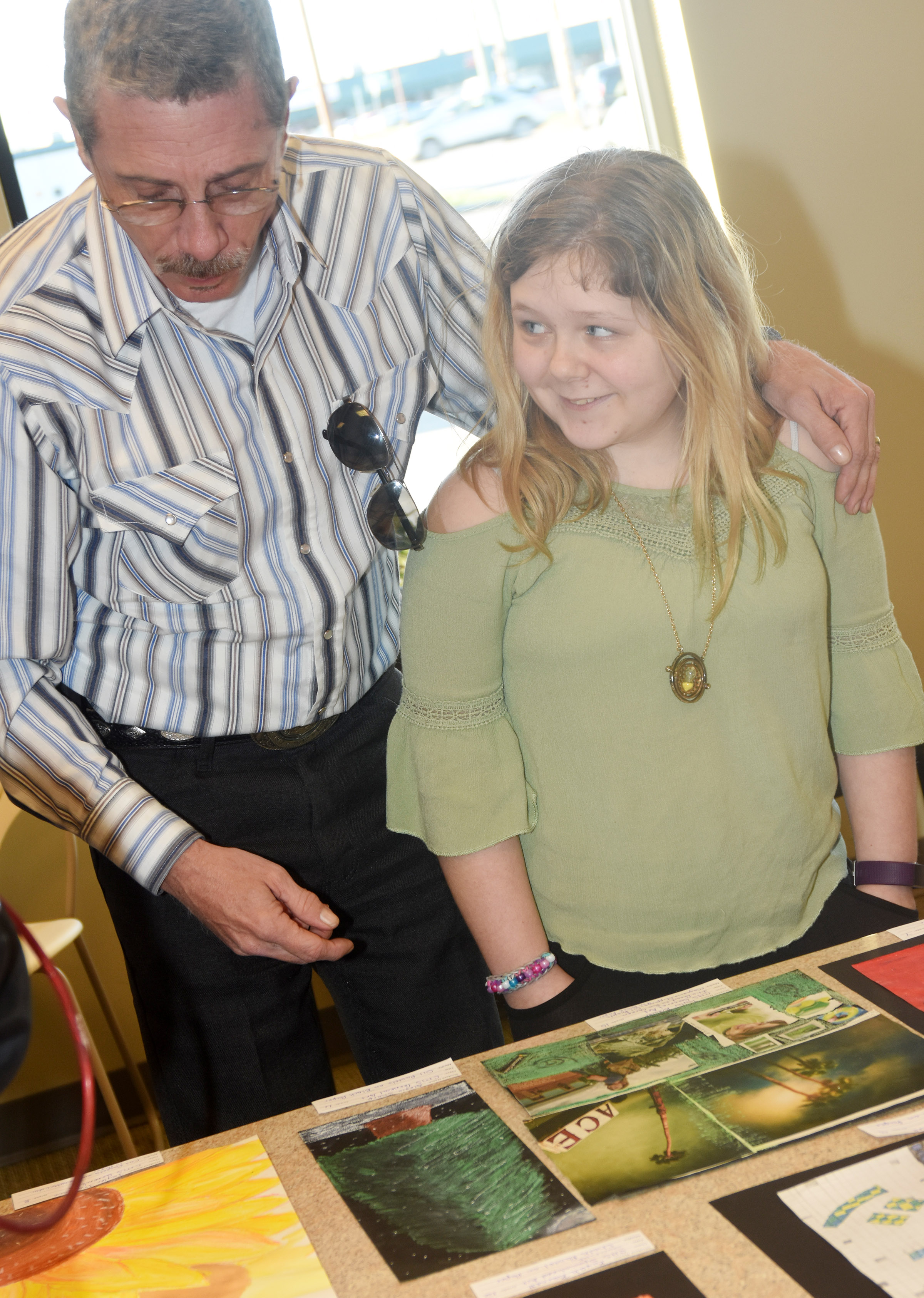 CMS sixth-grader Alexis Sharp looks at her artwork with her grandfather Greg.