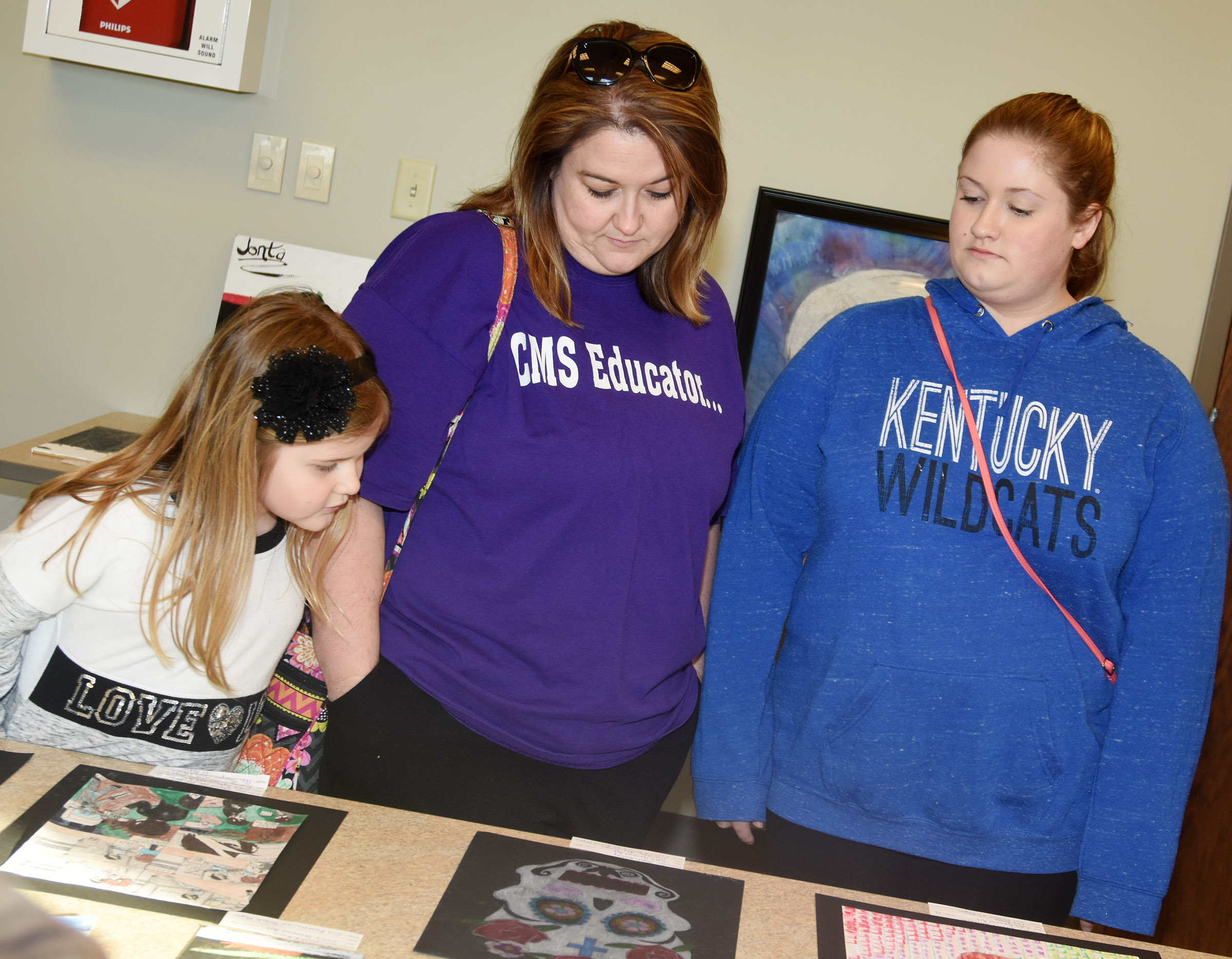 CHS sophomore Aleah Knifley, at right, looks at her artwork with her mother Amy and sister Aubreigh, a first-grader at Campbellsville Elementary School.