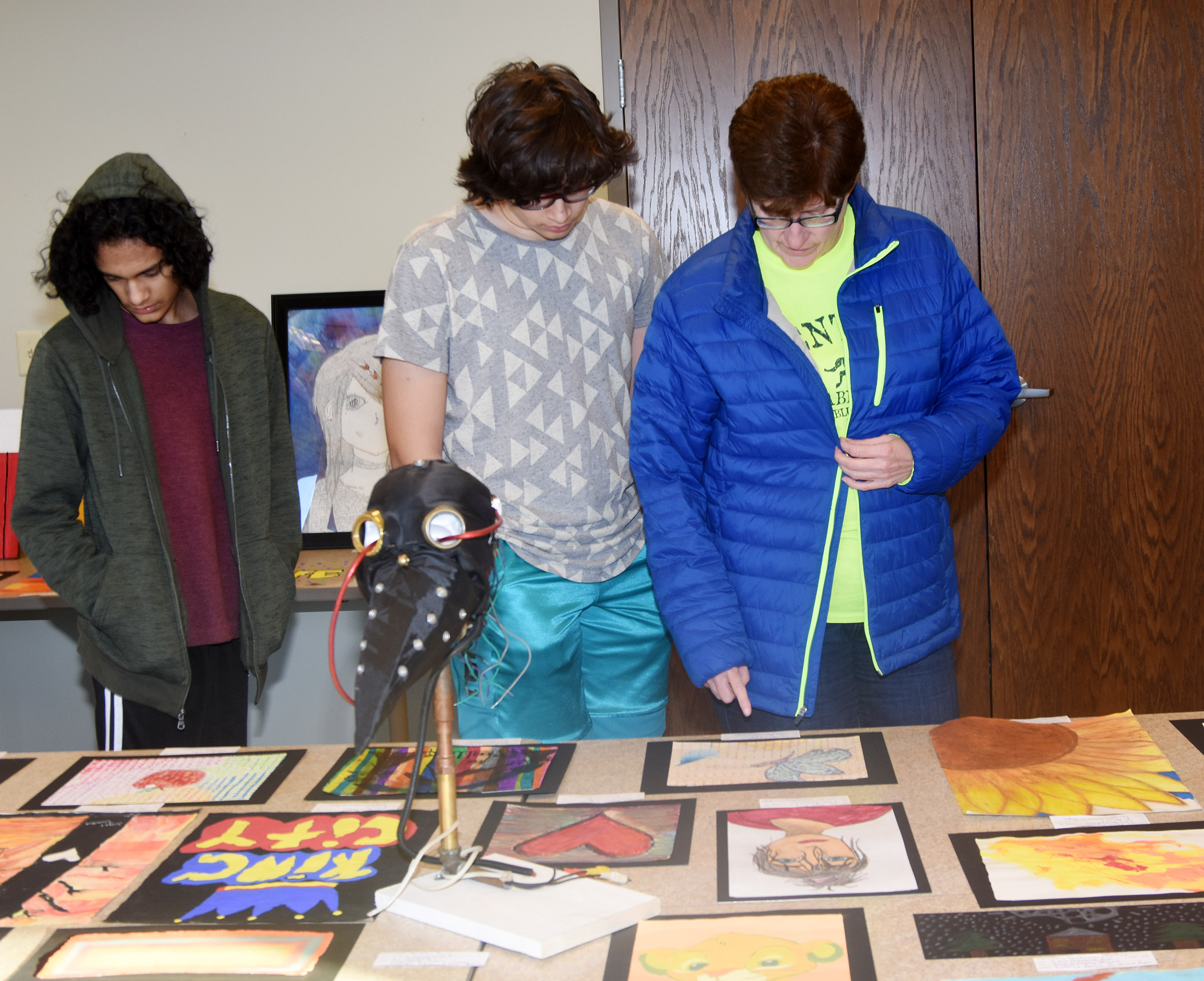 CMS eighth-grader Nate Arachi, center, looks at his artwork with his brother Ben, a sophomore, and mother Christine Sooriya-Arachchi.