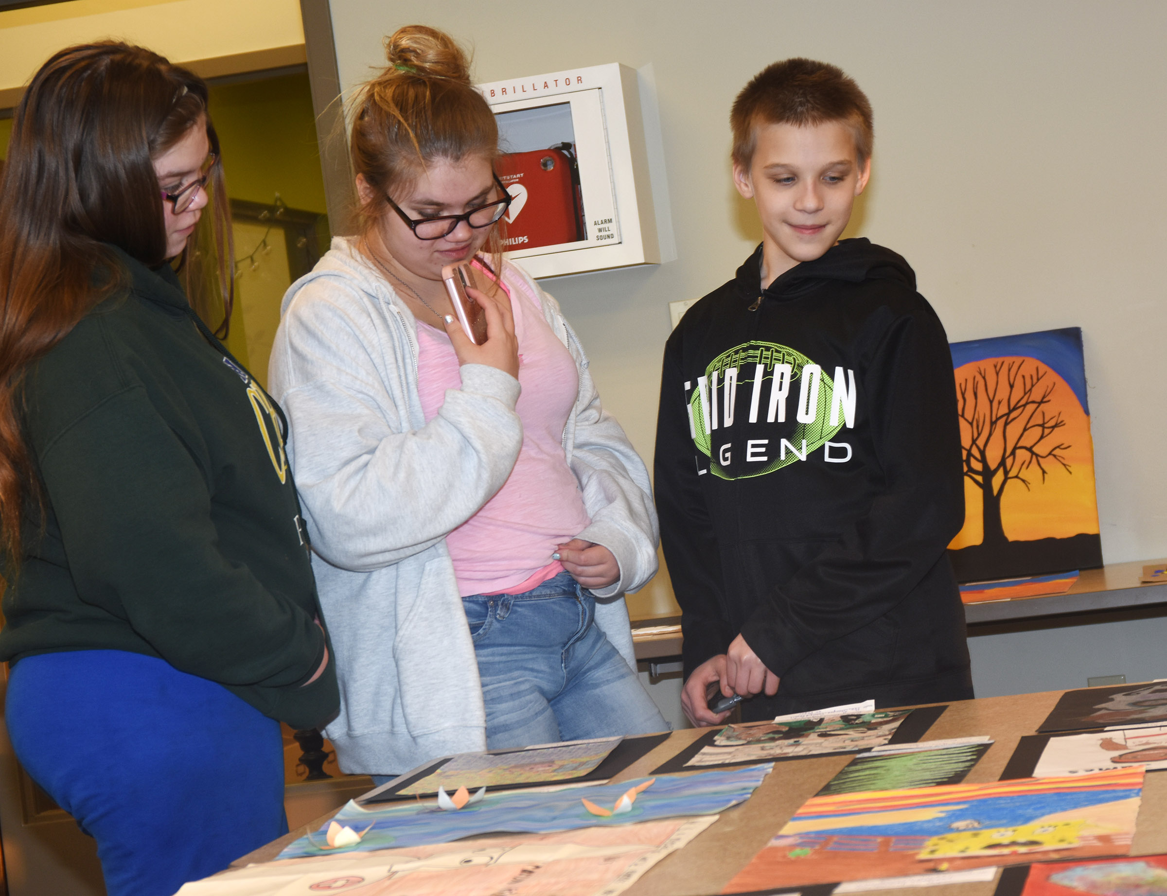 CHS junior Mackenzie Quackenbush, center, looks at her artwork with her sister Zoe, a freshman, and brother Kody, a sixth-grader.