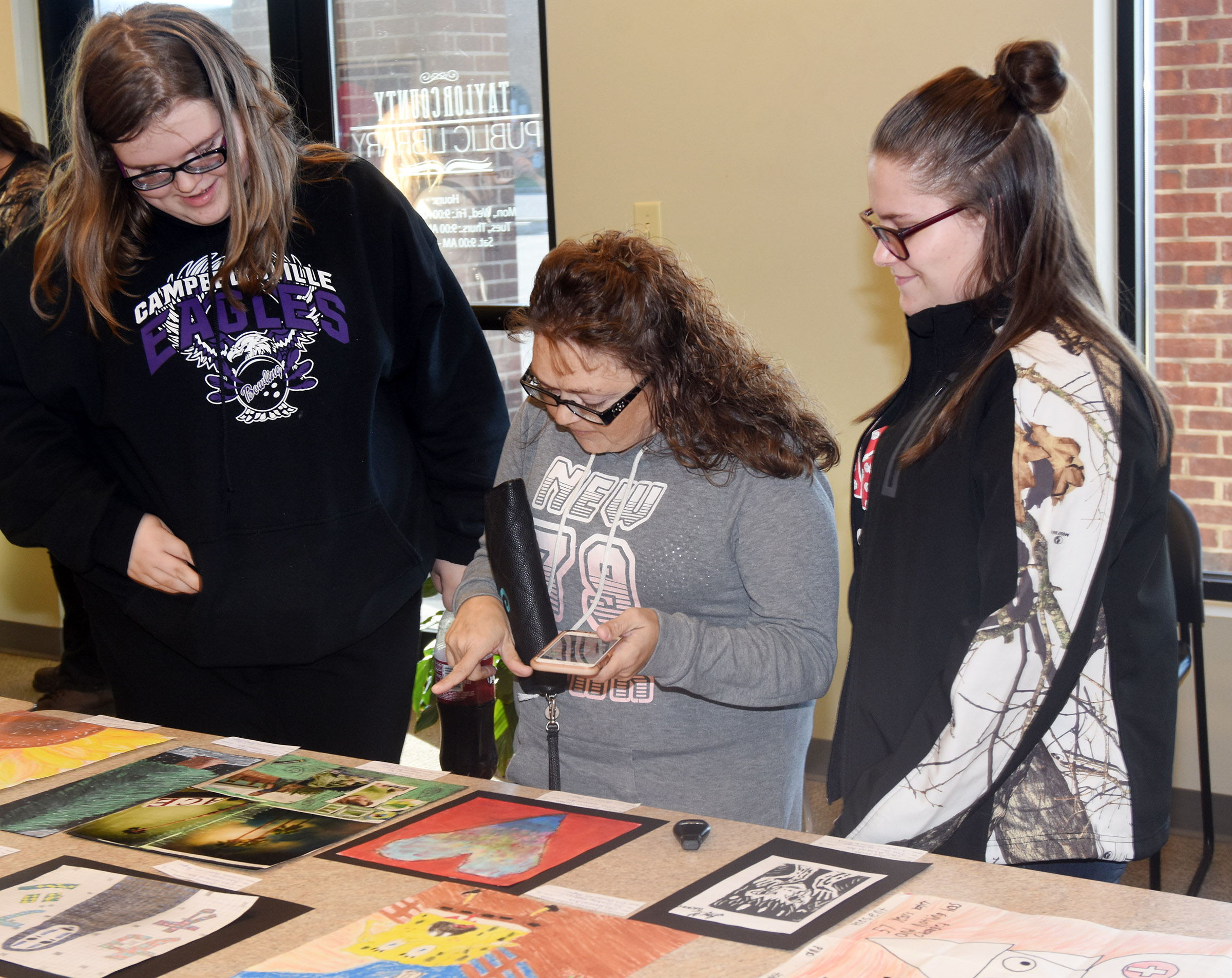 CHS freshman Taylor Brewer, at left, and sophomore Nevaeh Underwood look at artwork with Underwood's mother Tara.