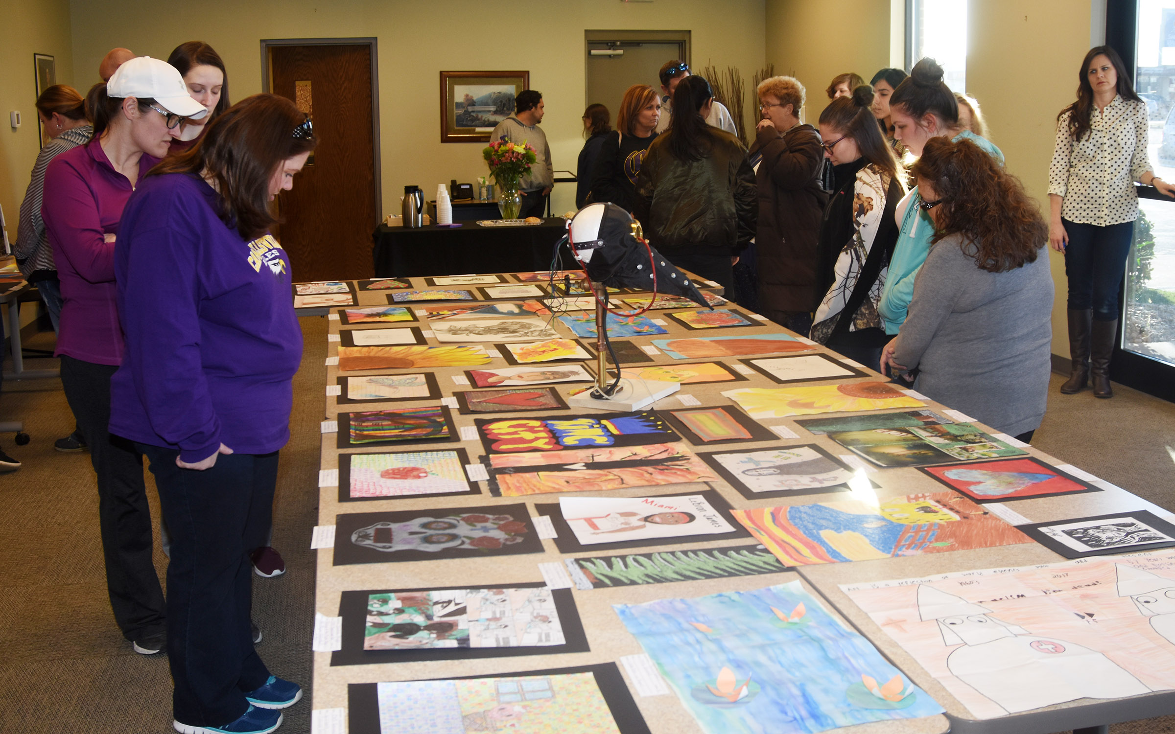 CMS and CHS teachers and students view the artwork on display.