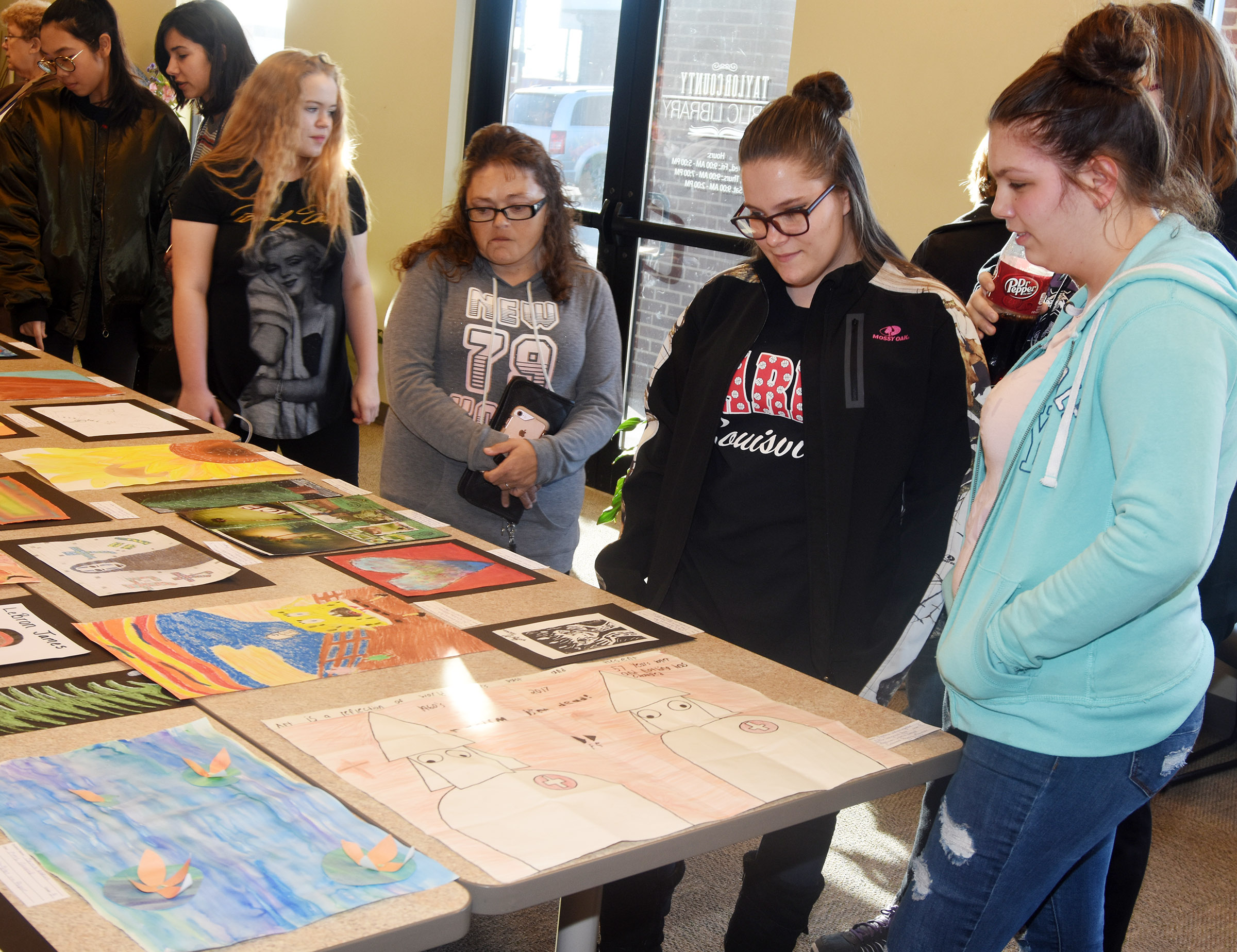 CHS sophomores Neveah Underwood, center, and Shelby Hunt look at the artwork.