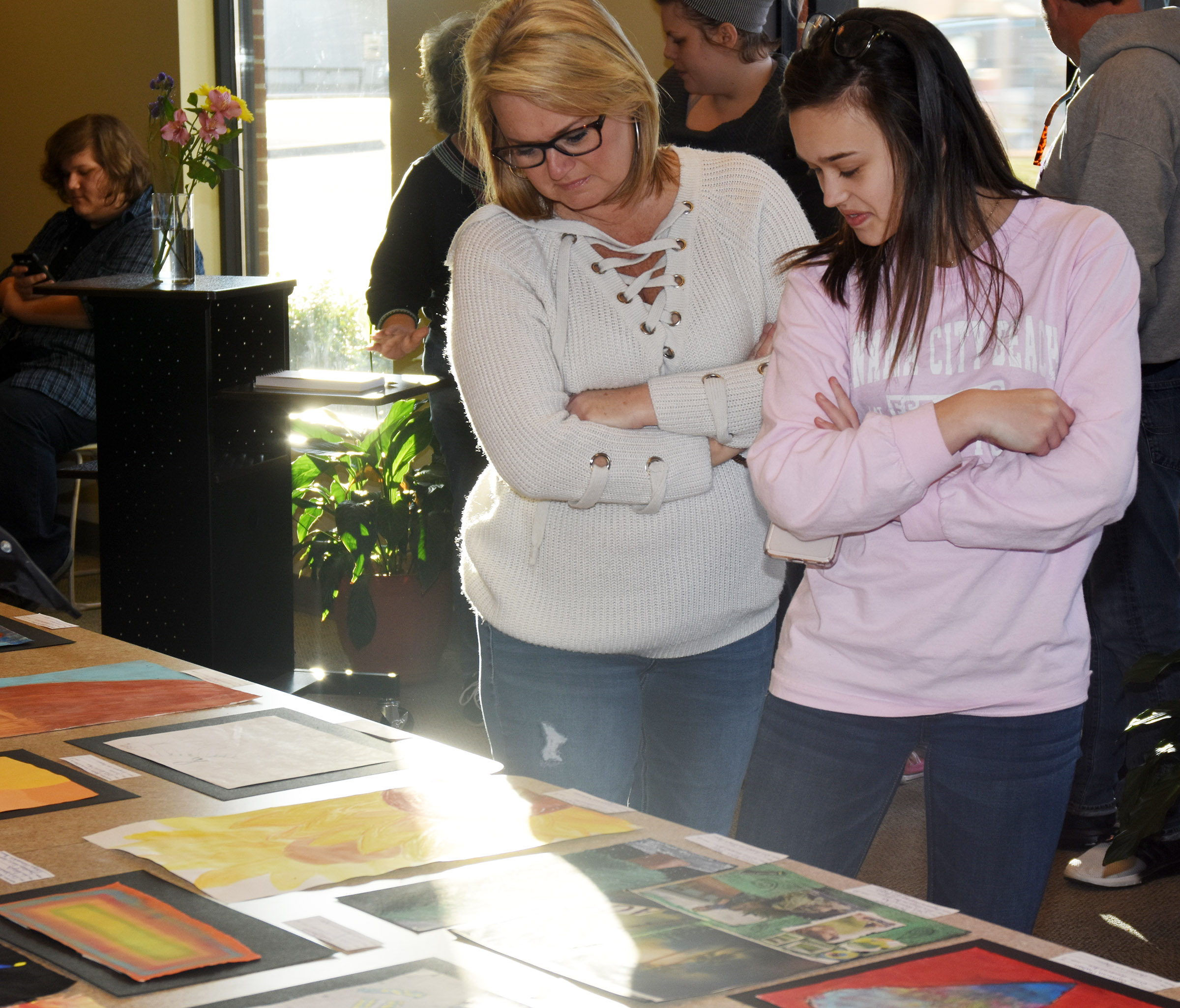 Campbellsville Middle School eighth-grader Tayler Thompson and her mother Kim look at the artwork on display.