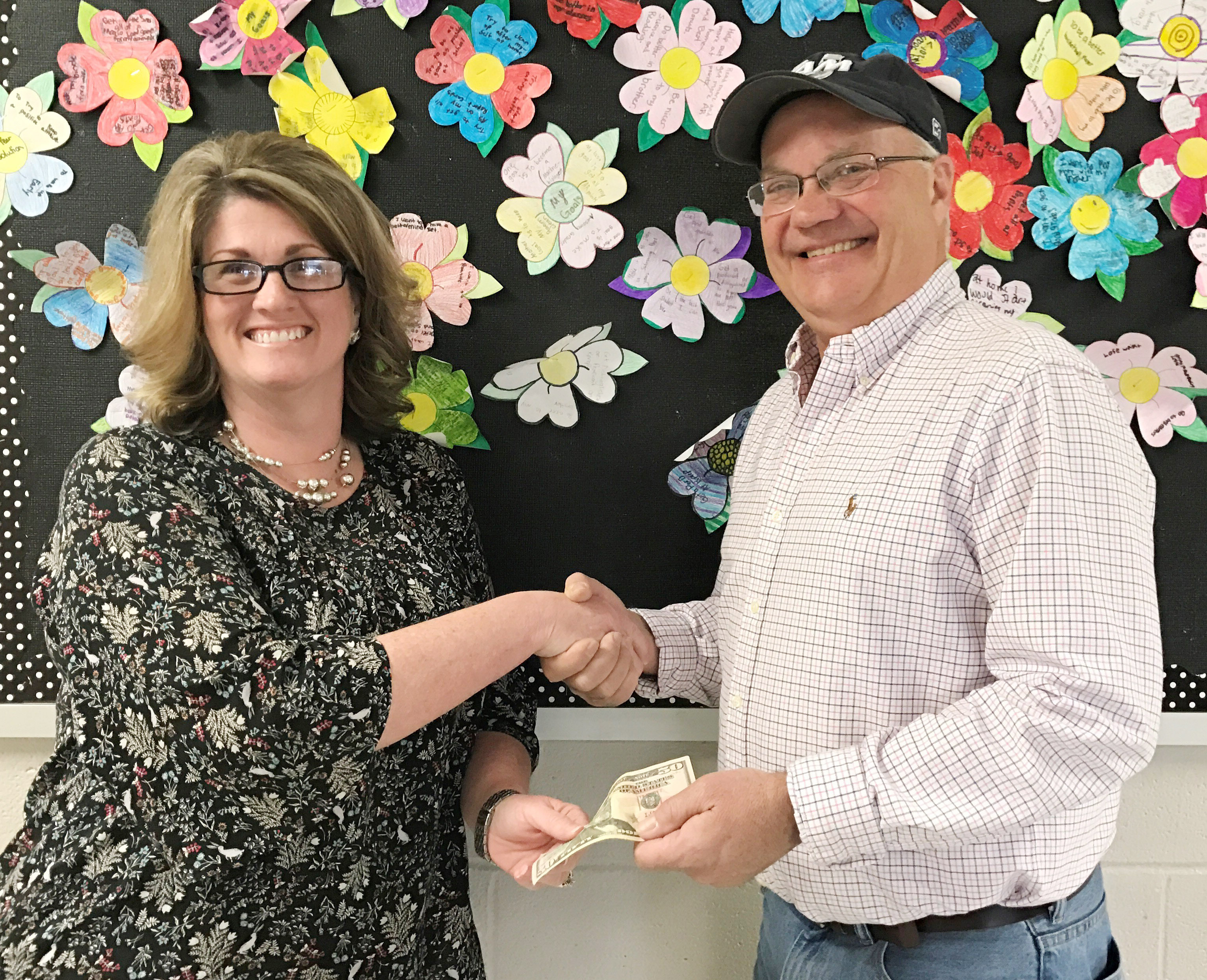 Taylor County Conservation District Board Member Barry Smith gives CMS fifth-grade teacher Donna White a $50 prize for her student Lillee Byrne being the overall CMS art contest winner.