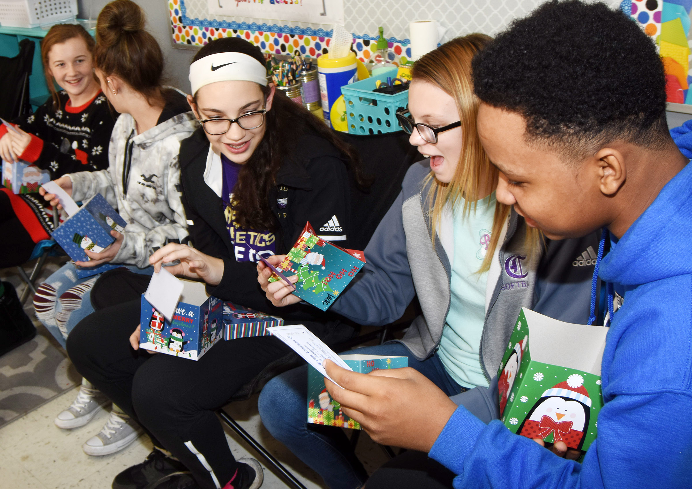 CMS eighth-grade students open their Christmas gifts, donated by local community members. From left are Dakota Slone, Alexis Byers, Mary Russell, Jade Wheeler and Deondre Weathers.