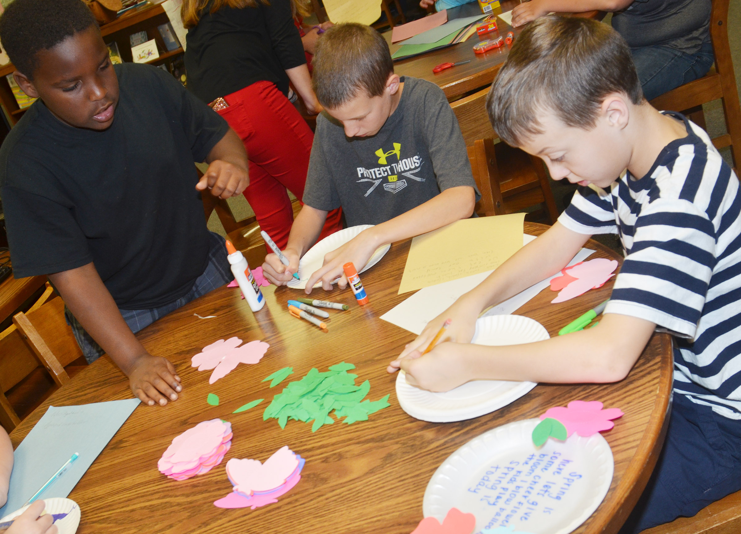 CMS fourth-graders, from left, Temarieon Warren, Rowan Petett and Noah Skaggs write their poems on paper plates.
