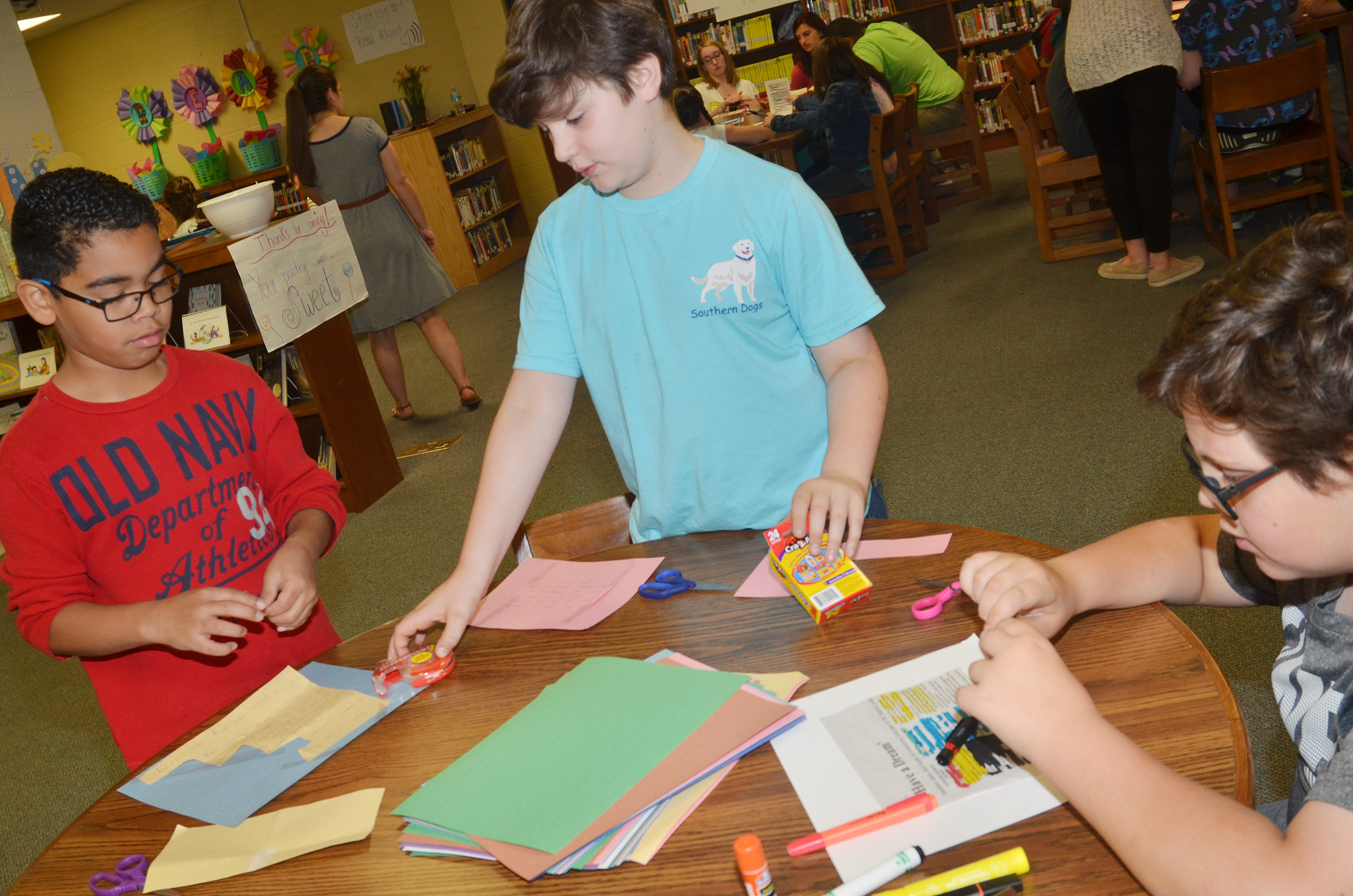 From left, CMS fourth-graders Gabriel Noyola, Andrew Mardis and Landon Arnett illustrate their poems.