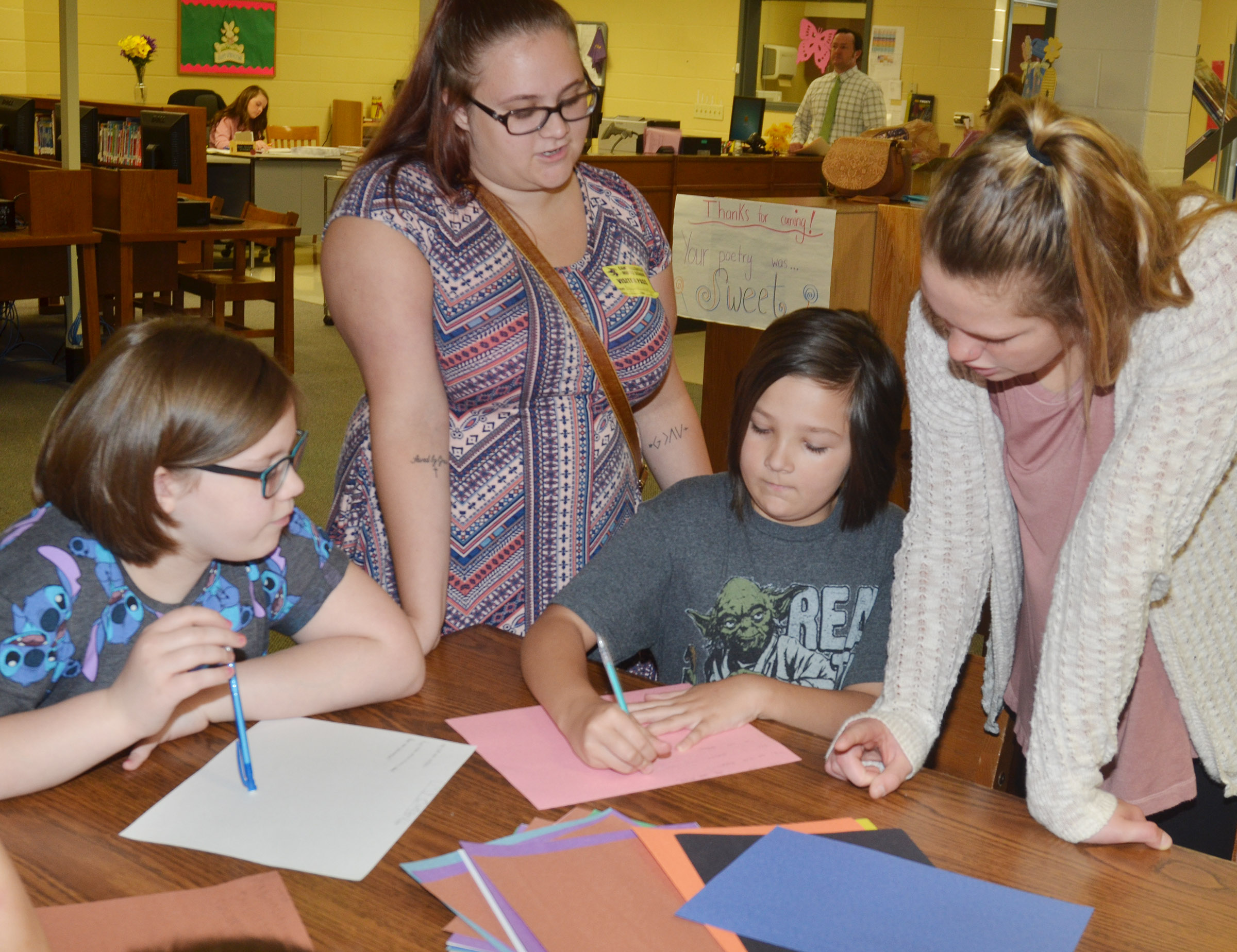 CMS fourth-graders Kaylyn Lawson, at left, and Cassie Crick write their poetry with some help from CU students.