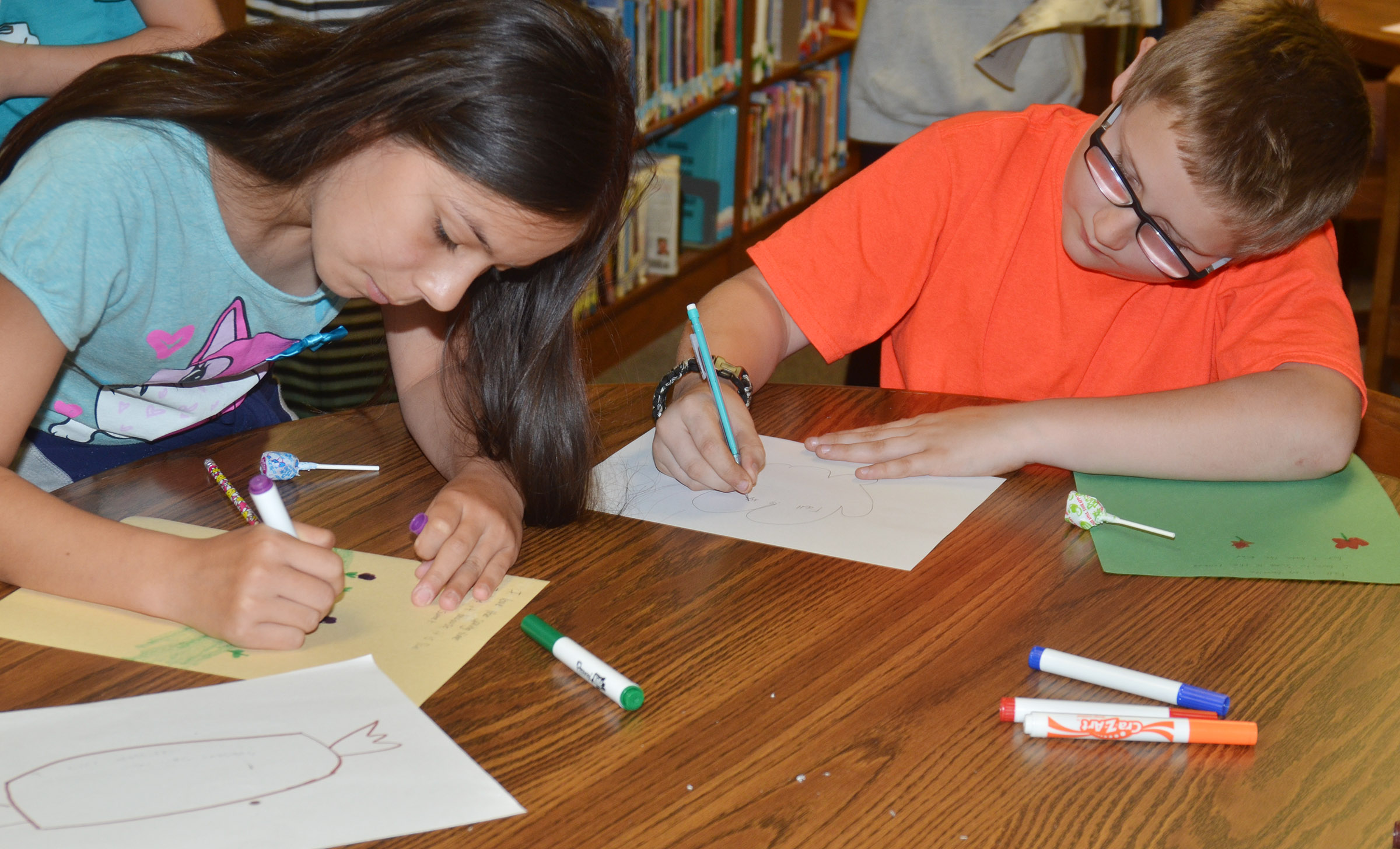 CMS fourth-graders Marissa Segura, at left, and Landon Rakes illustrate their poetry.