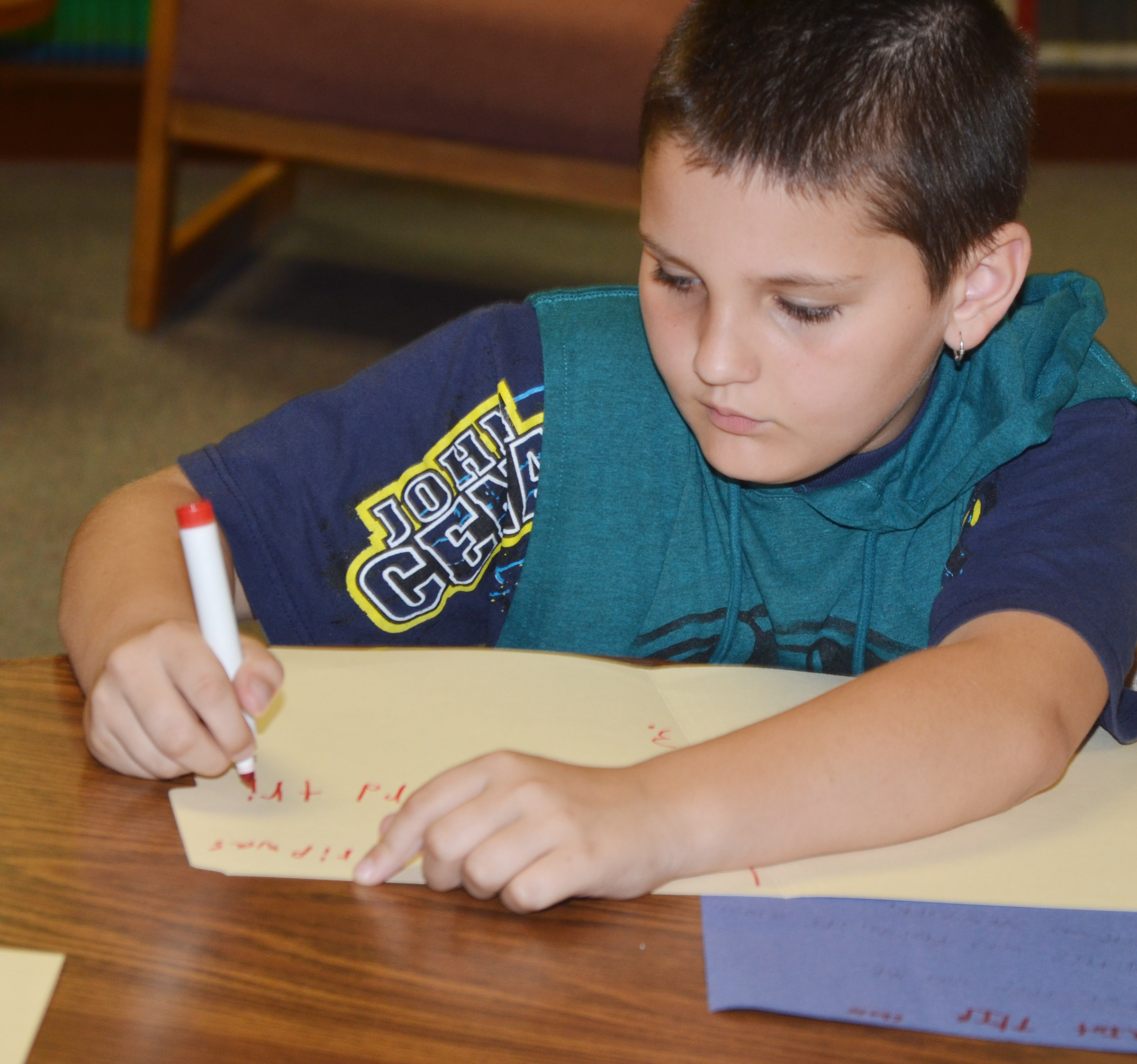 CMS fourth-grader Chase Gabehart writes his poem.