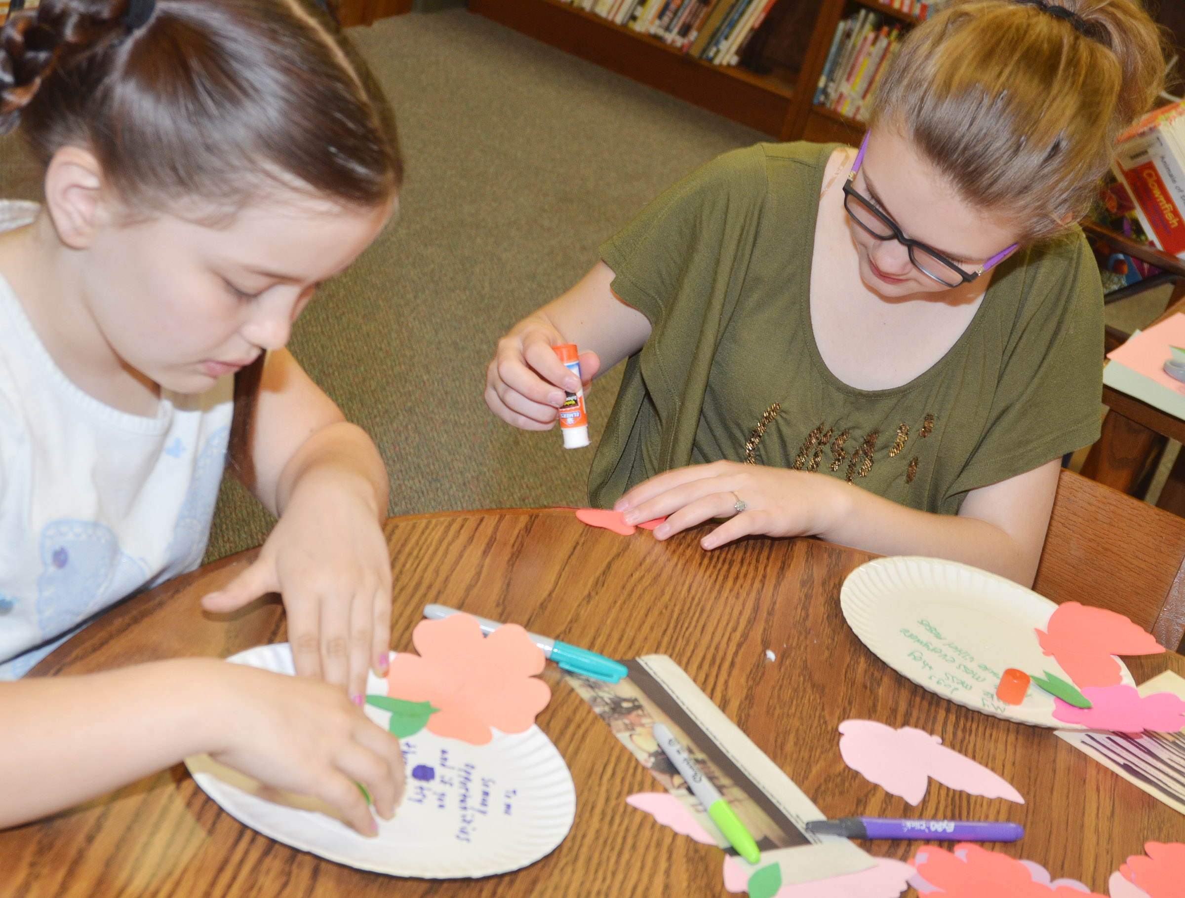 CMS fourth-graders Kate Billeter, at left, and Autumn Jones decorate the paper plates on which they wrote their poems.