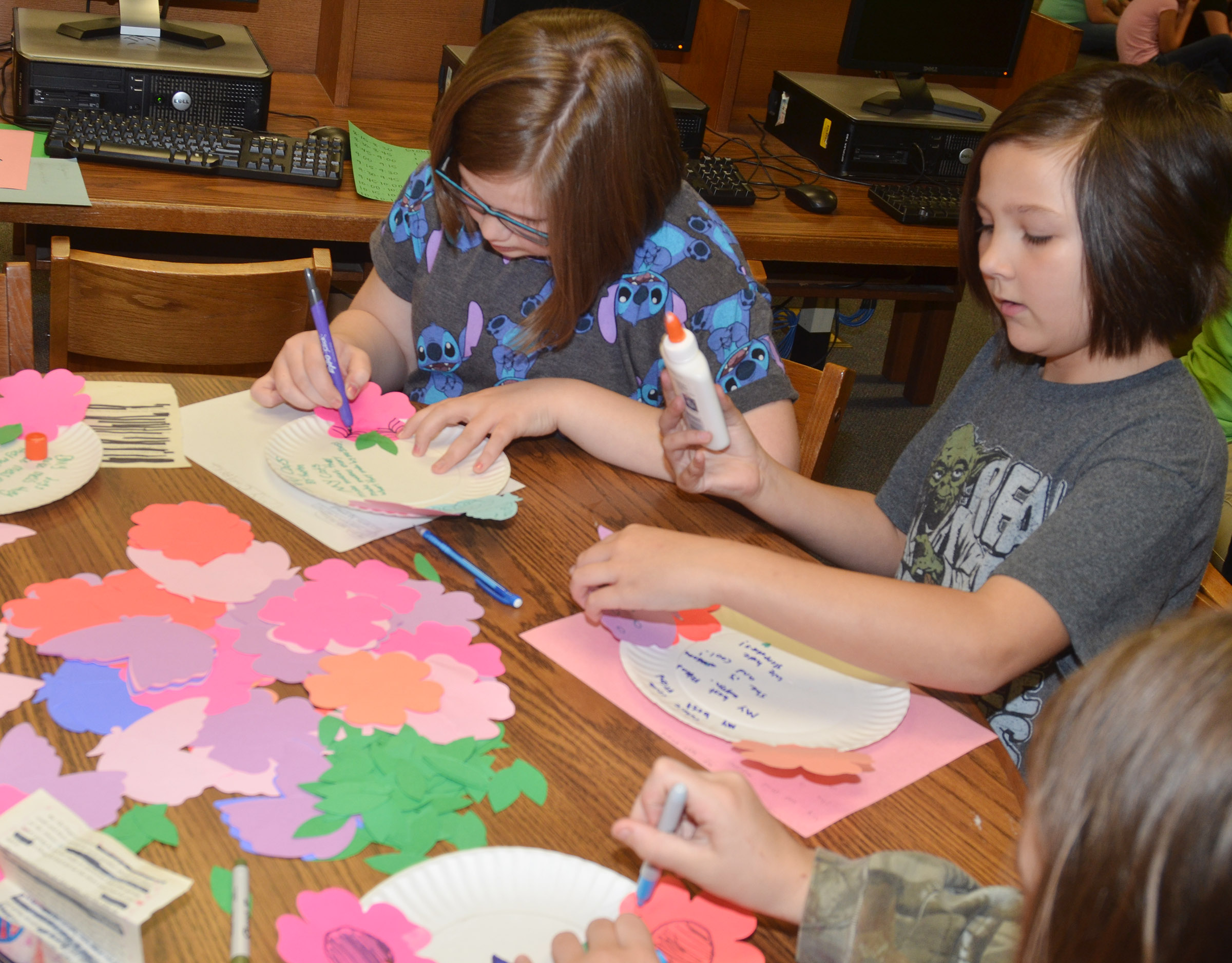 CMS fourth-graders Kaylyn Lawson, at left, and Cassie Crick decorate the paper plates on which they wrote their poems.