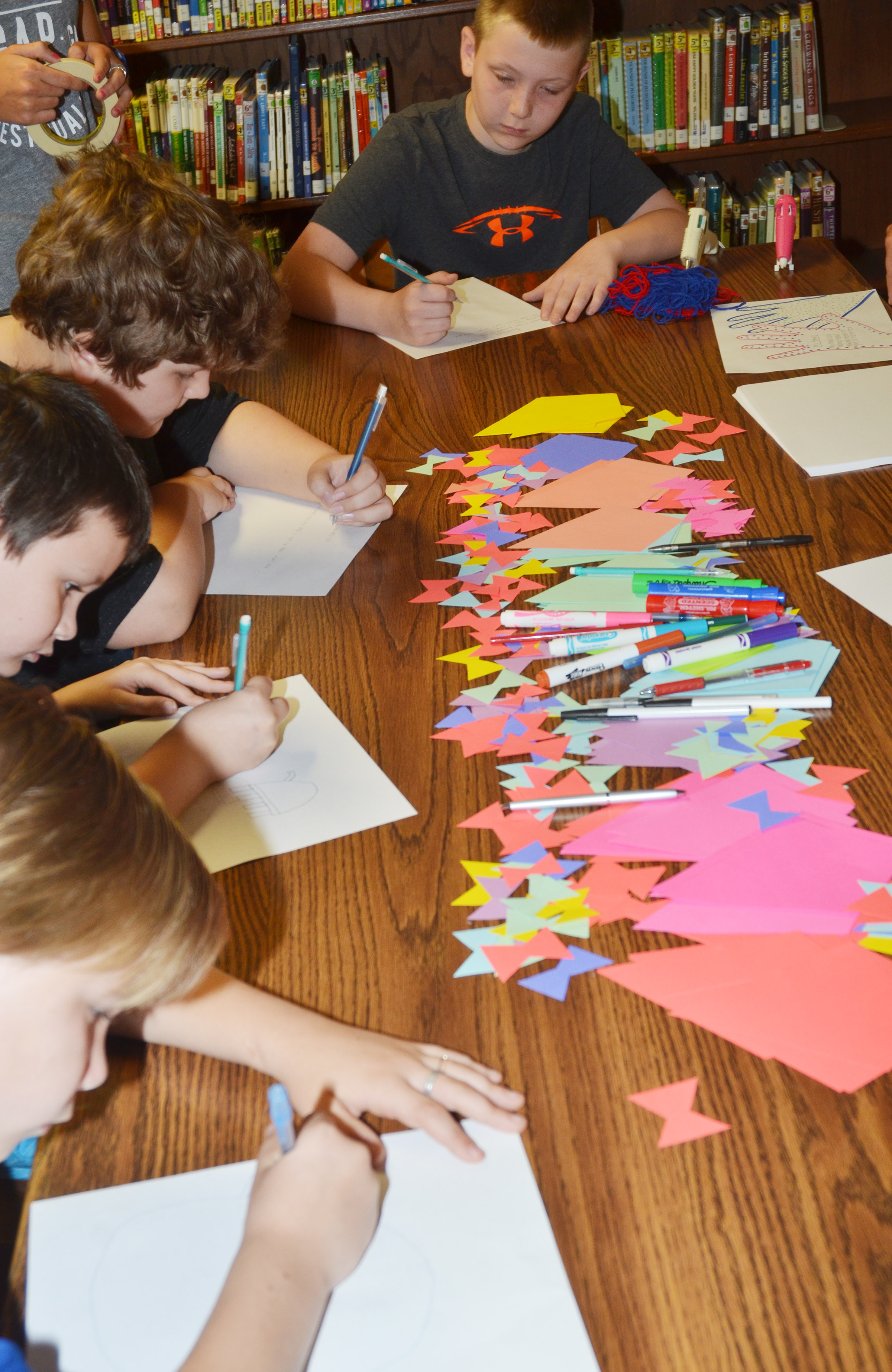 CMS fourth-graders write their free verse poems. When finished, they will illustrate them.
