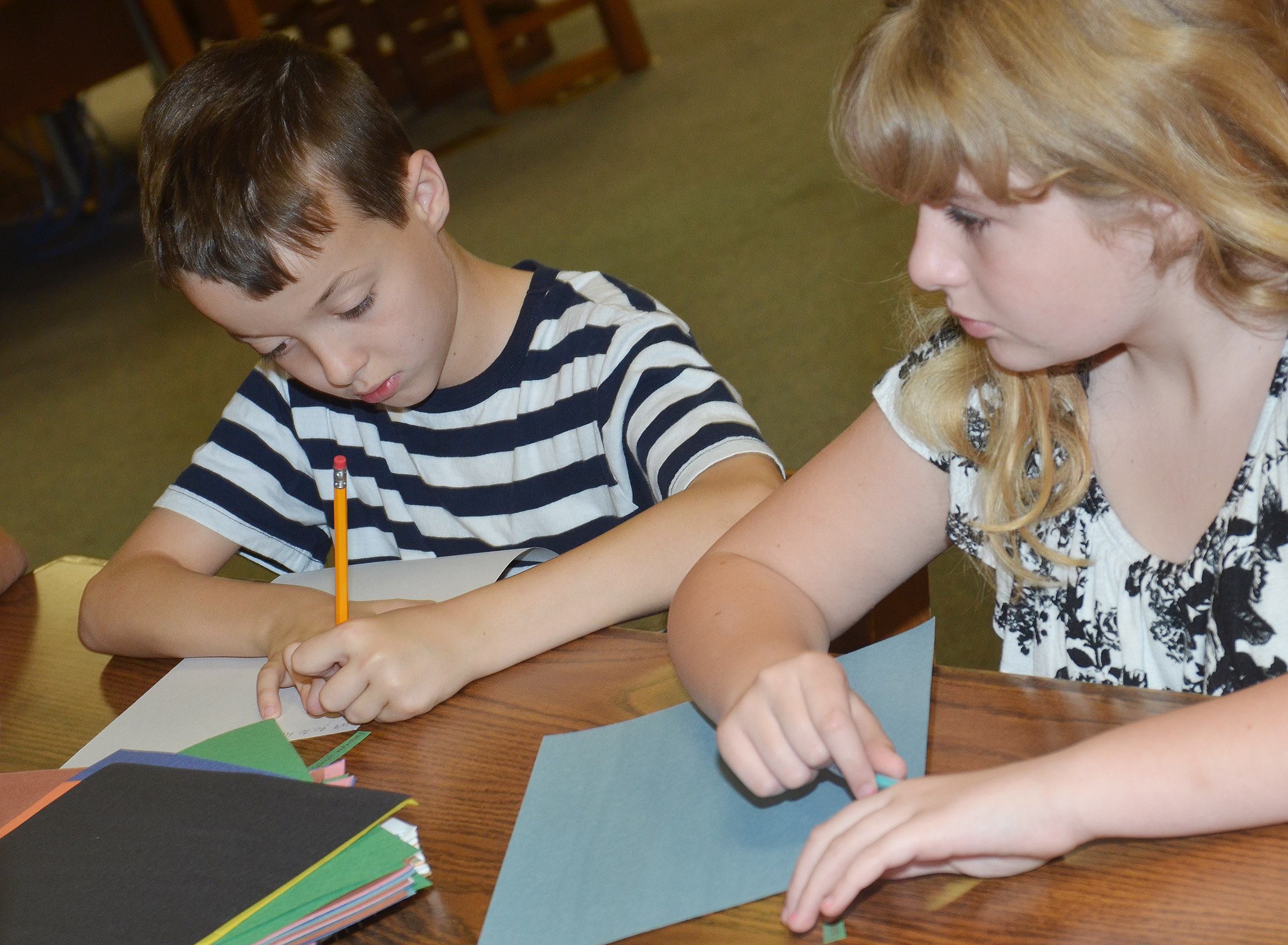 CMS fourth-graders Noah Skaggs, at left, and Dakota Broyles write their free verse poems.