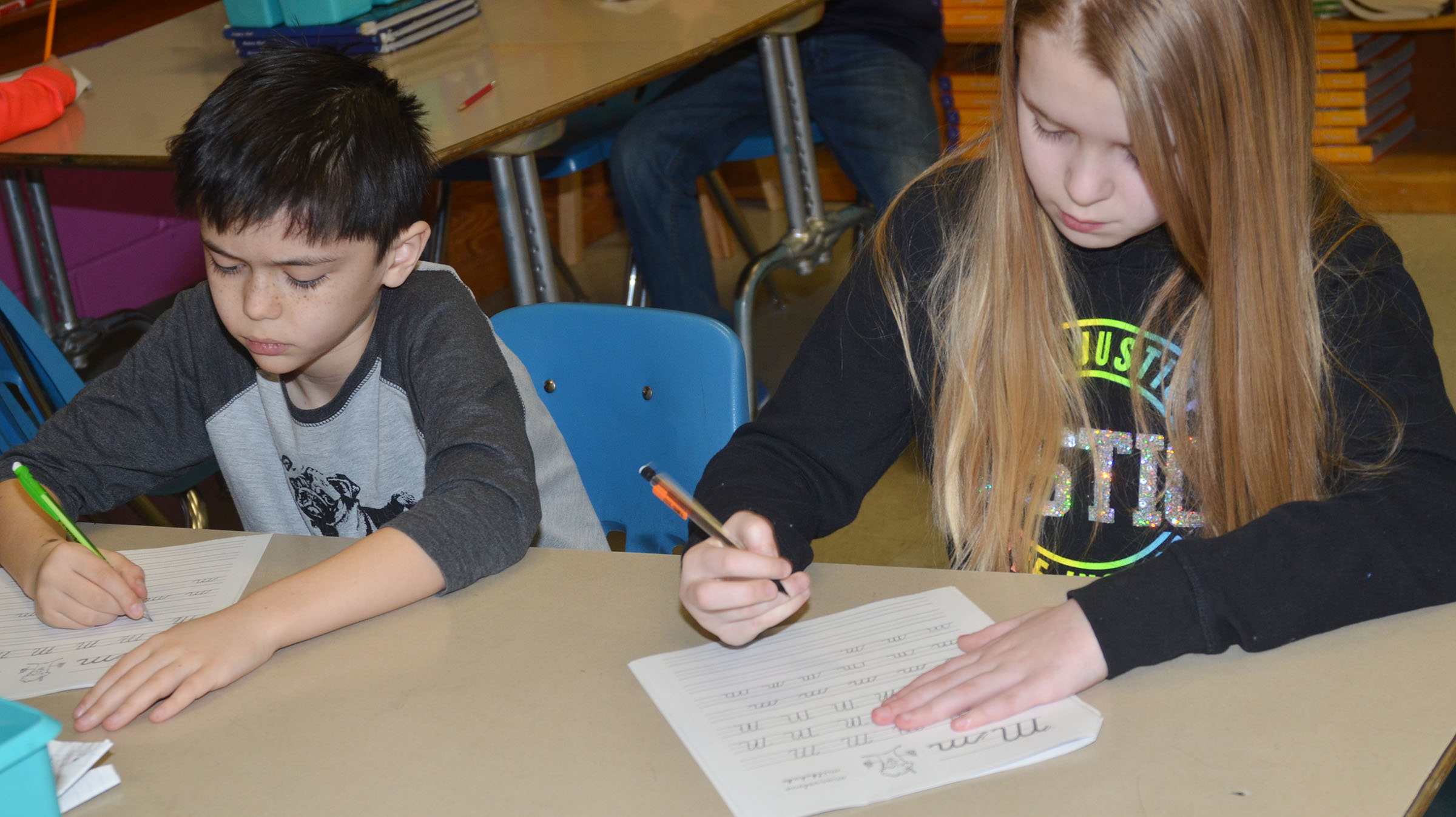 CMS fifth-graders Isacc Billeter, at left, and Jaylie Moore practice cursive writing.