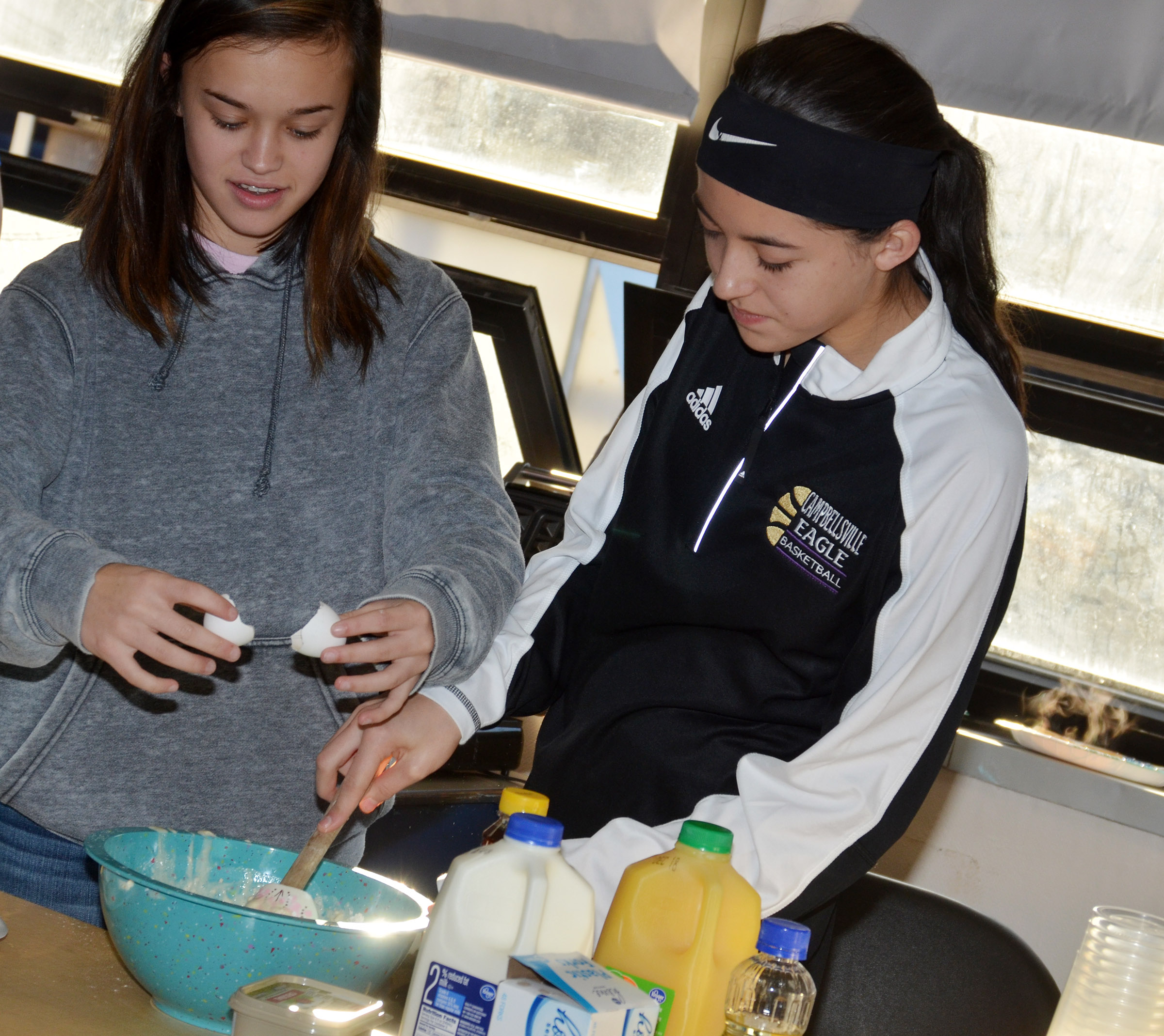 CMS eighth-graders Tayler Thompson, at left, and Kaylyn Smith demonstrate how to make waffles.