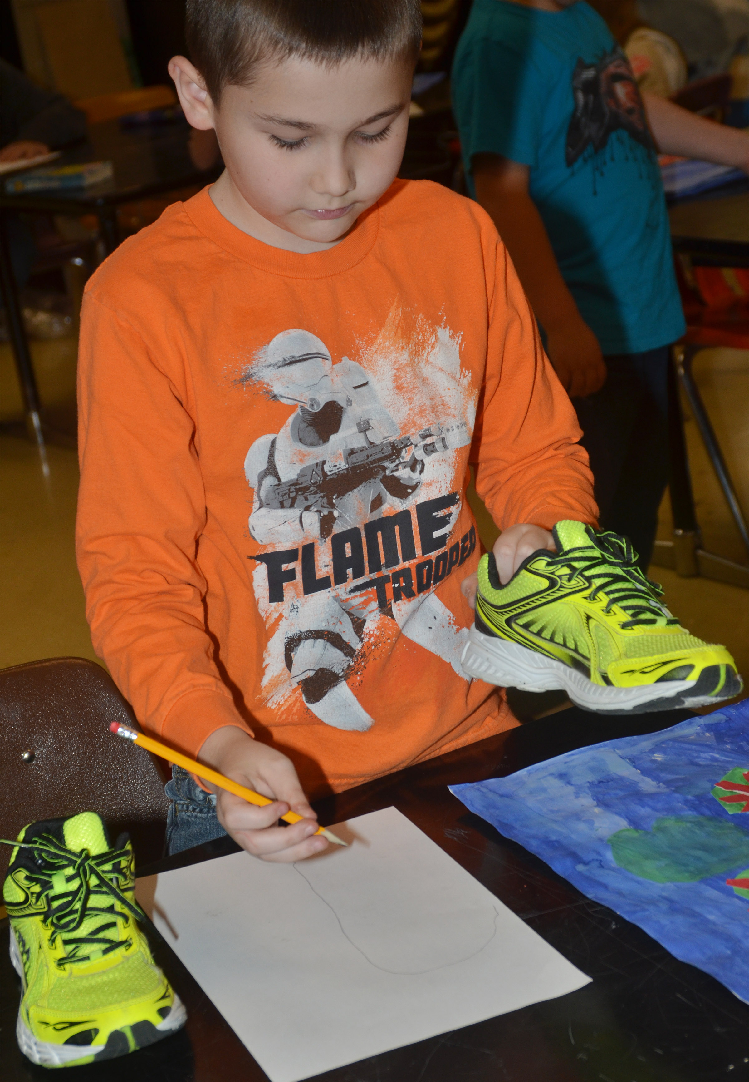 CMS fourth-grader Michael Abel traces his shoes to draw himself using the foreshortening technique.