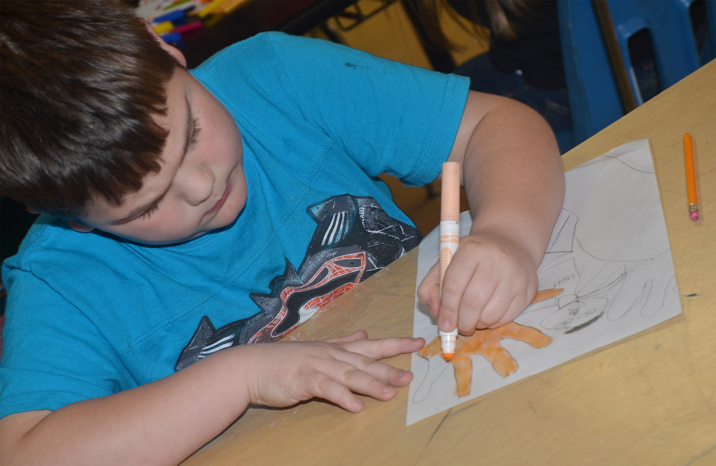 CMS fourth-grader Logan England colors his drawing using the foreshortening technique.