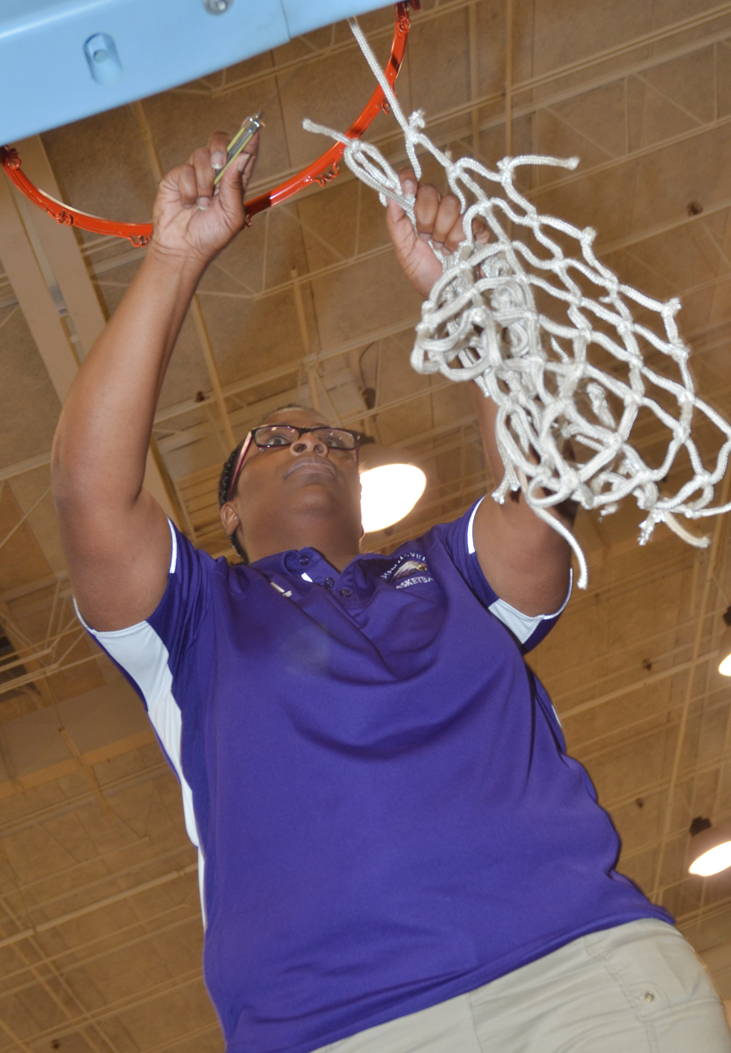 Campbellsville Middle School girls' eighth-grade basketball team recently won its first Central Kentucky Middle School Athletic Conference tournament championship title in 20 years. Above, CMS girls' basketball head coach Tiarra Cecil cuts down the championship net.