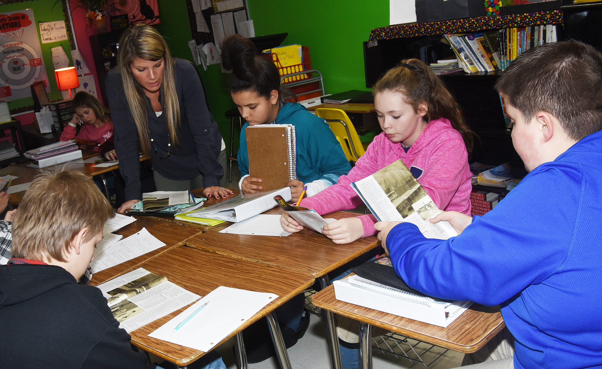 CMS teacher Andrea Gribbins talks with, from left, sixth-graders Gracie Taylor, CheyAnn Edwards and Luke McDonald about how to find details in a story that support the main idea.
