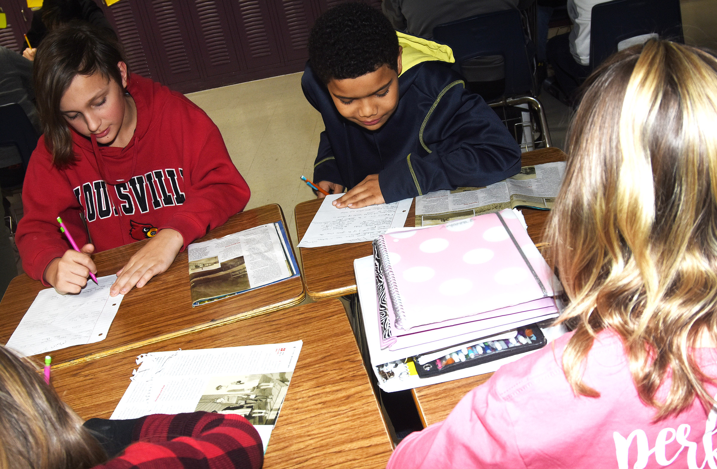 CMS sixth-graders Ethan Taylor, at left, and Tashaun Hart work with their group members to find the main idea in a story.