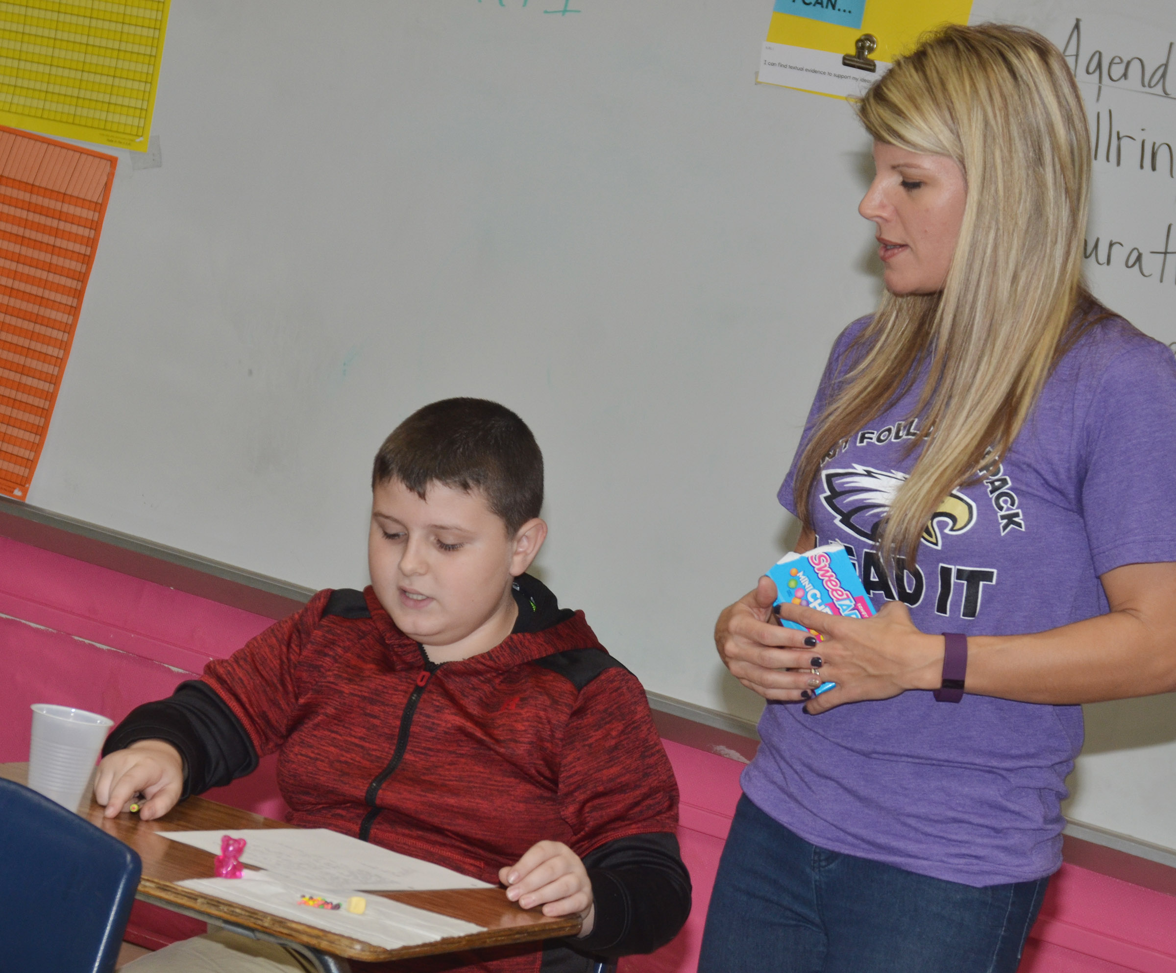 CMS sixth-grade teacher Andrea Gribbins talks to Dawson Creason as he uses alliterations and similes to describe his sweet and tart candies.