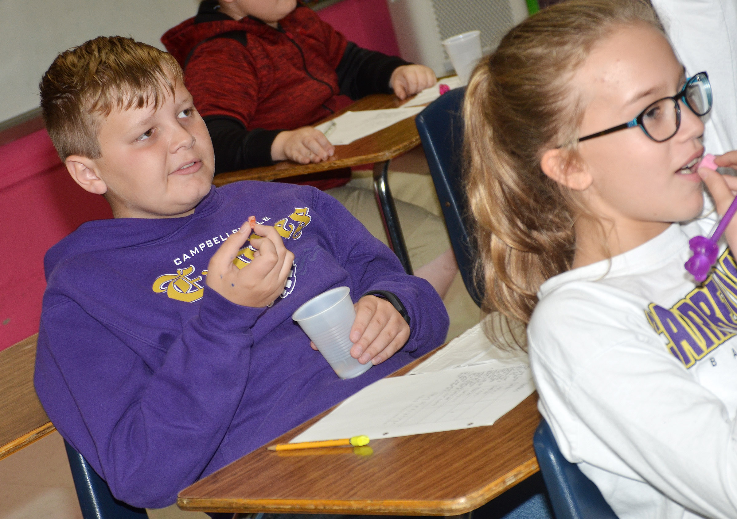 CMS sixth-graders Hunter Falls, at left, and Chloe Thompson try some sweet and tart candies.