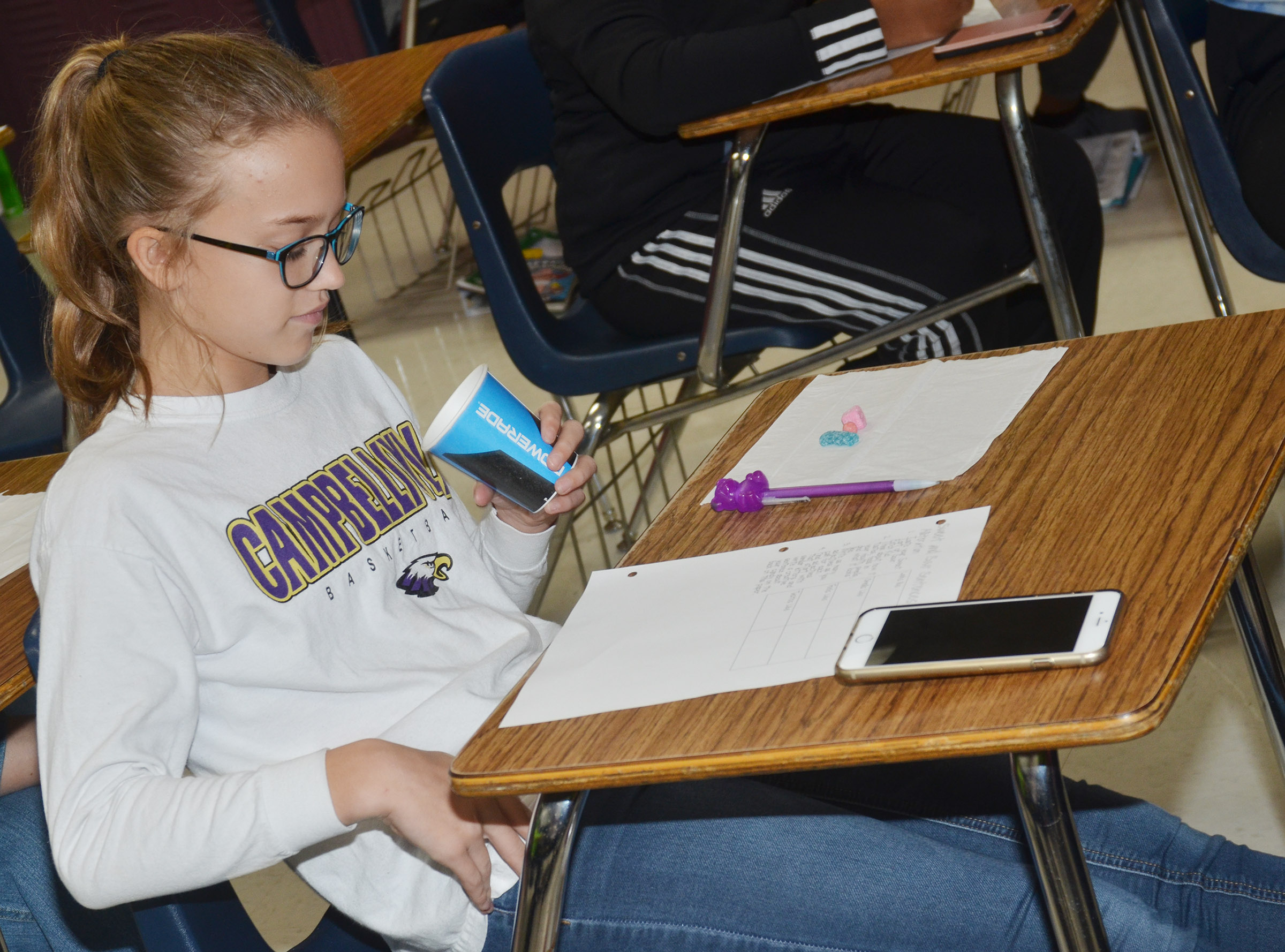 CMS sixth-grader Chloe Thompson tries sweet and tart candies as she practices writing alliterations and similes.