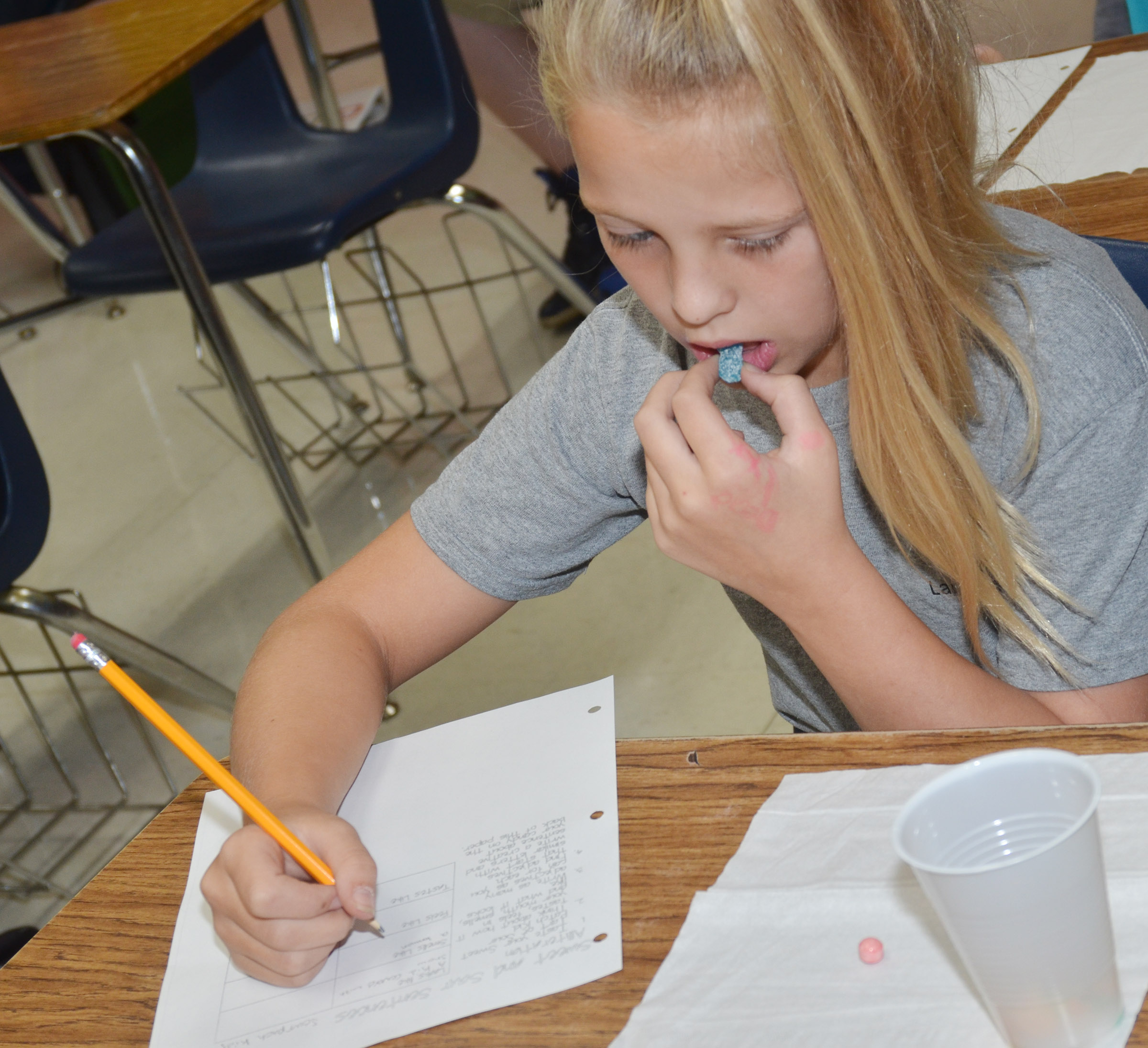 CMS sixth-grader Gabby Bright tries sweet and tart candies as she practices writing alliterations and similes.