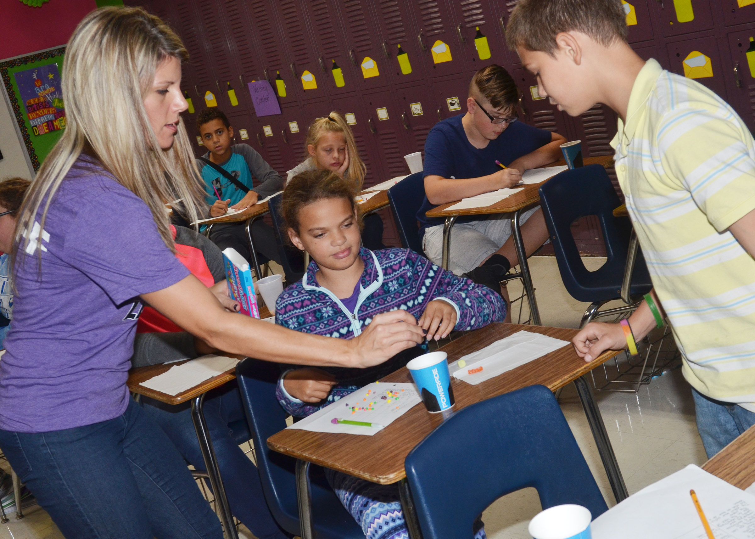 CMS sixth-grade teacher Andrea Gribbins passes out sweet and tart candies to Arisha Francis and Ashtan Forrest.