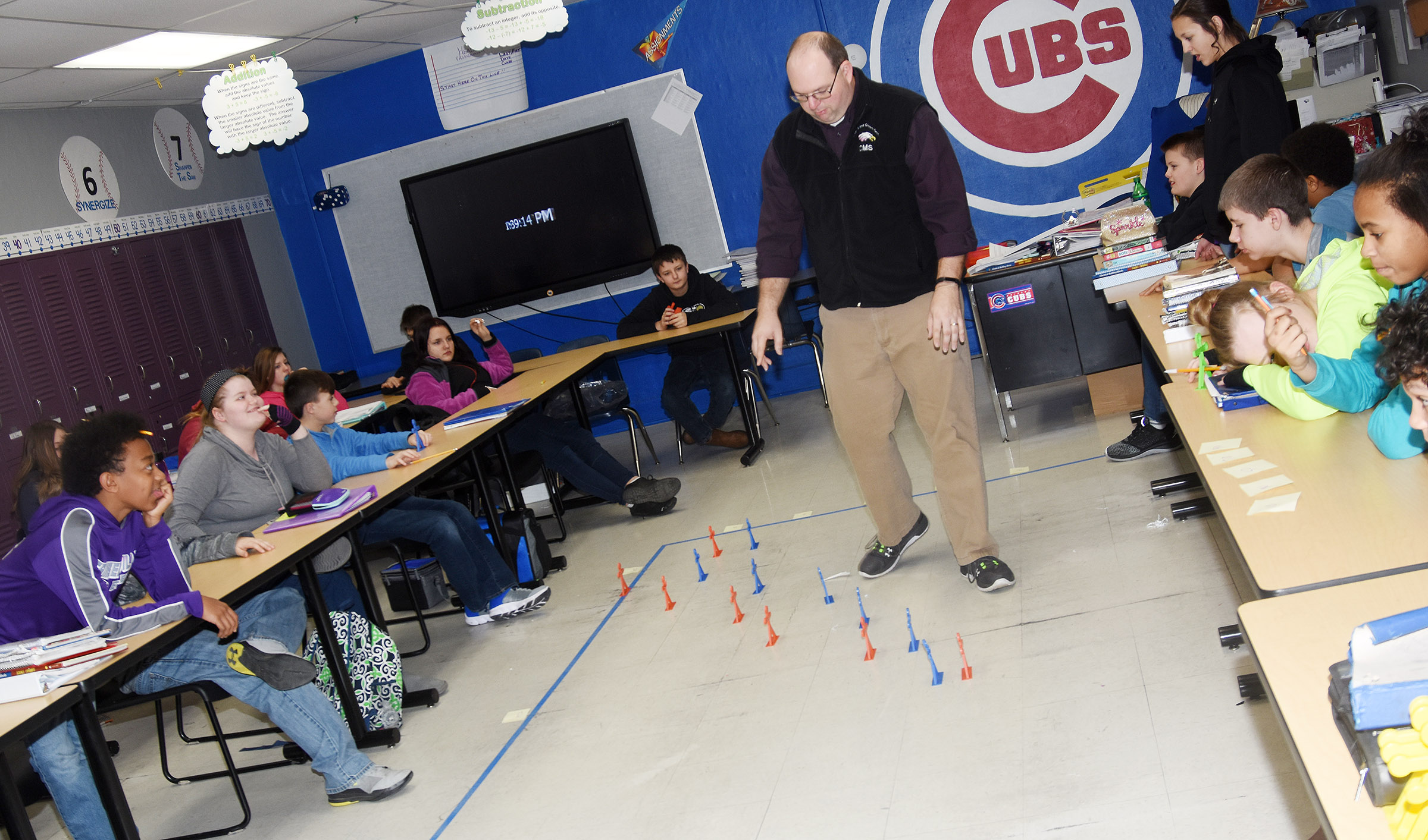 CMS teacher Steven Gumm talks to his students about how they can use a graph to organize and analyze information, and uses a life-size graph as an example.
