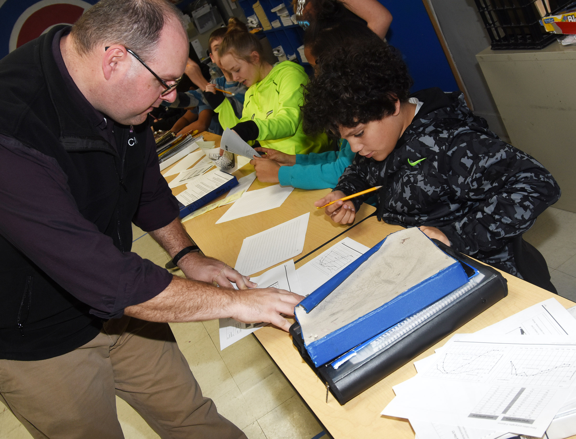CMS teacher Steven Gumm helps seventh-grader Kaydon Taylor as he creates his own graph to compare data.