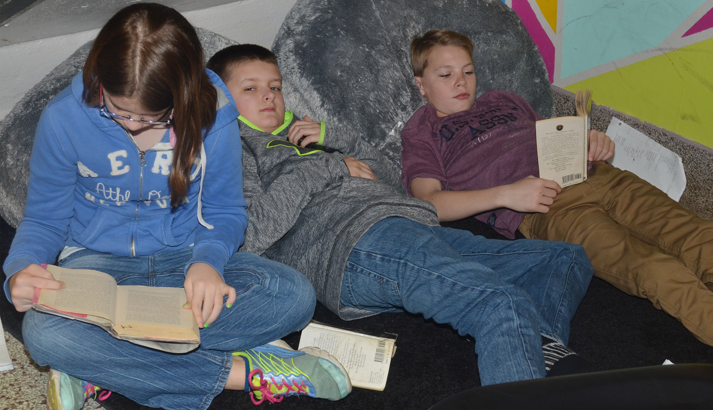 From left, CMS sixth-graders Liberty Albrecht and Tyler Booth and seventh-grader Tuff Harper read together.