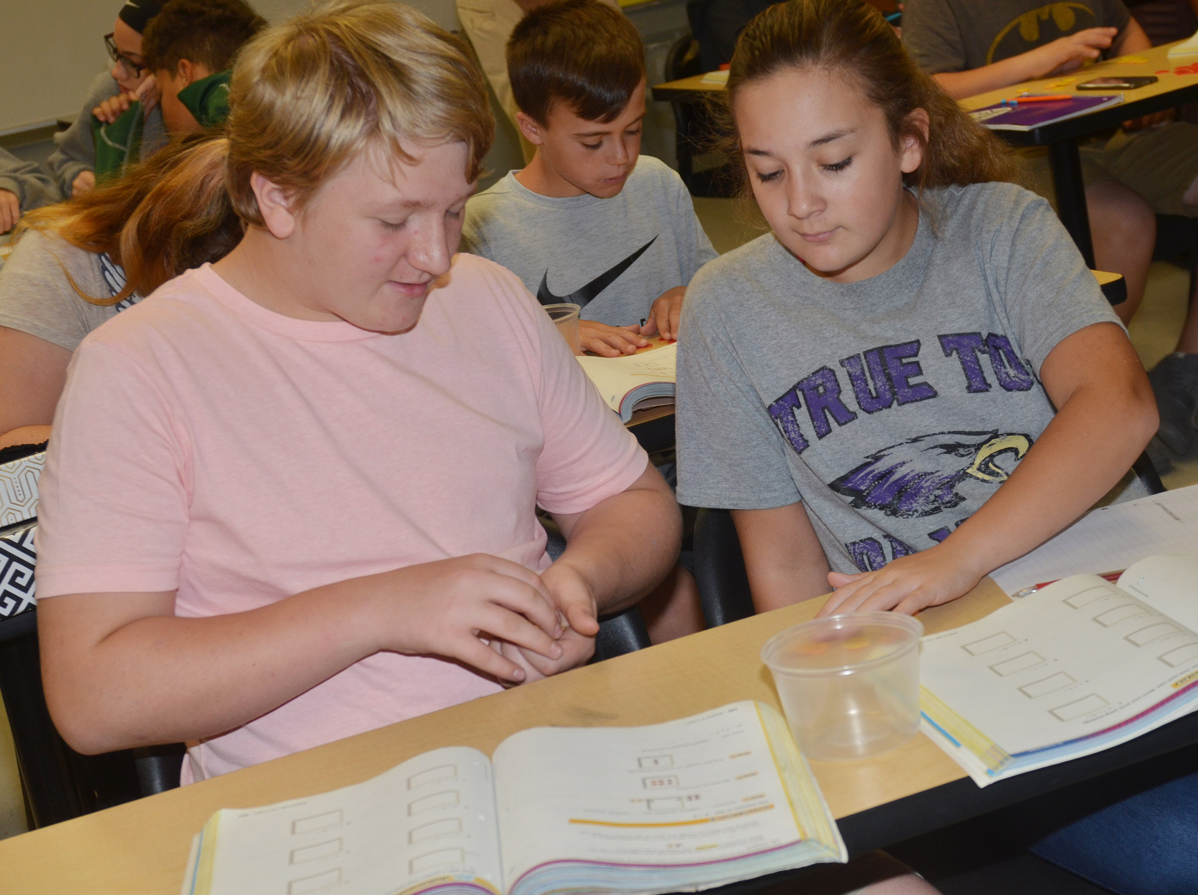 CMS seventh-graders Levi Dicken, at left, and Briana Davis work a math problem with their counters.