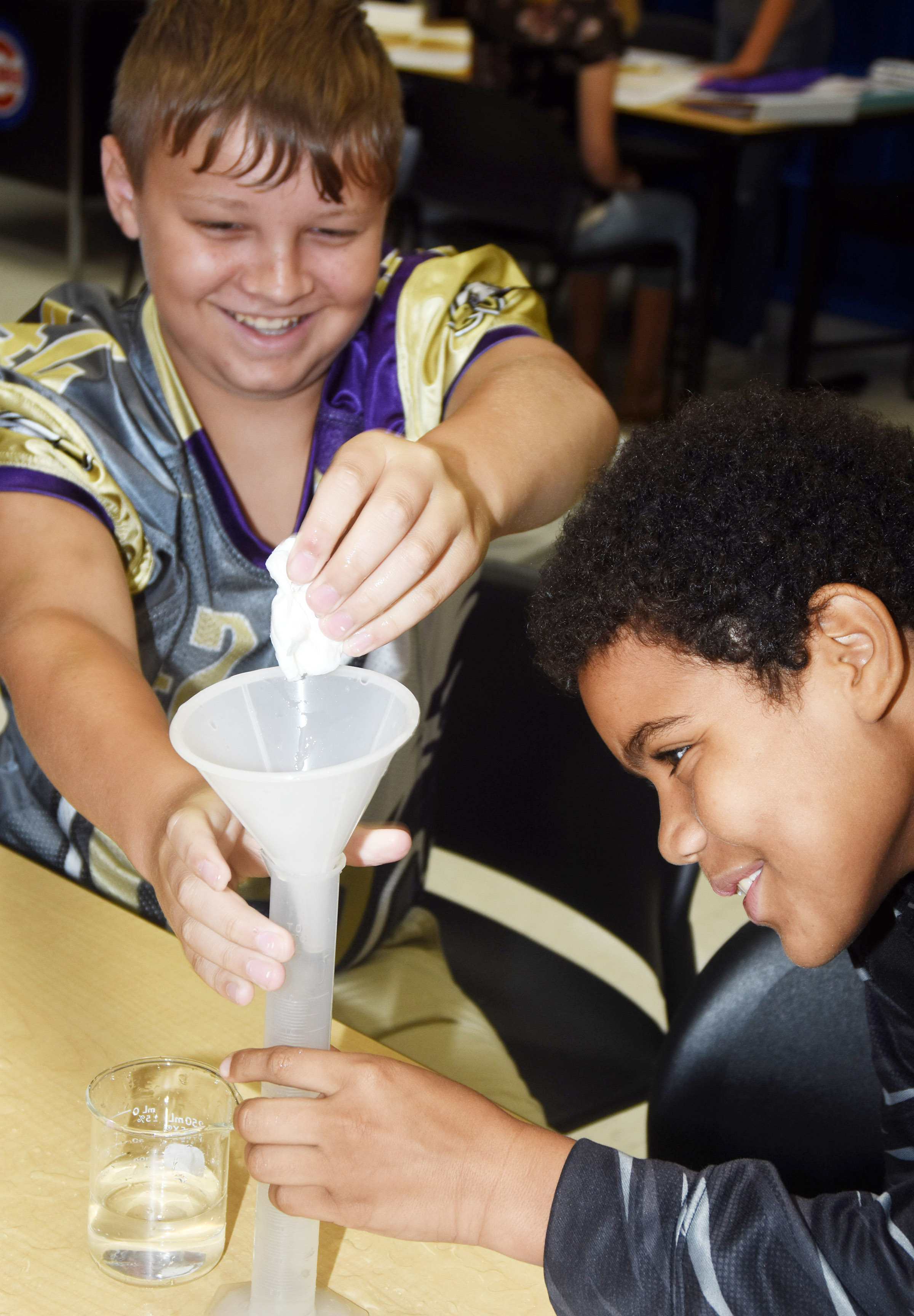 CMS seventh-graders Hunter Falls, at left, and Tashaun Hart squeeze water out of a paper towel to test its absorbency.