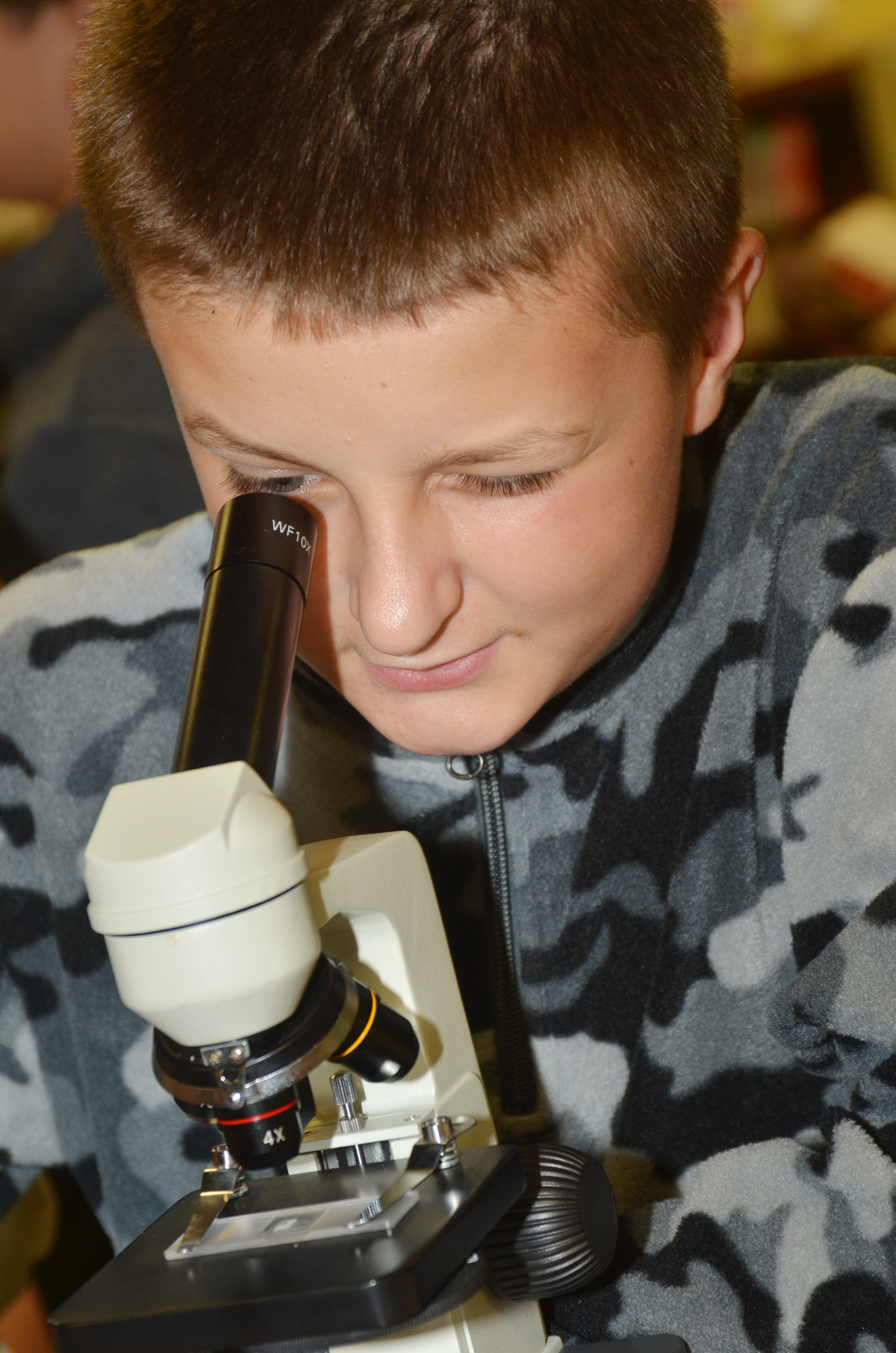 CMS seventh-grader Tyler Booth looks at a piece of onion under a microscope.