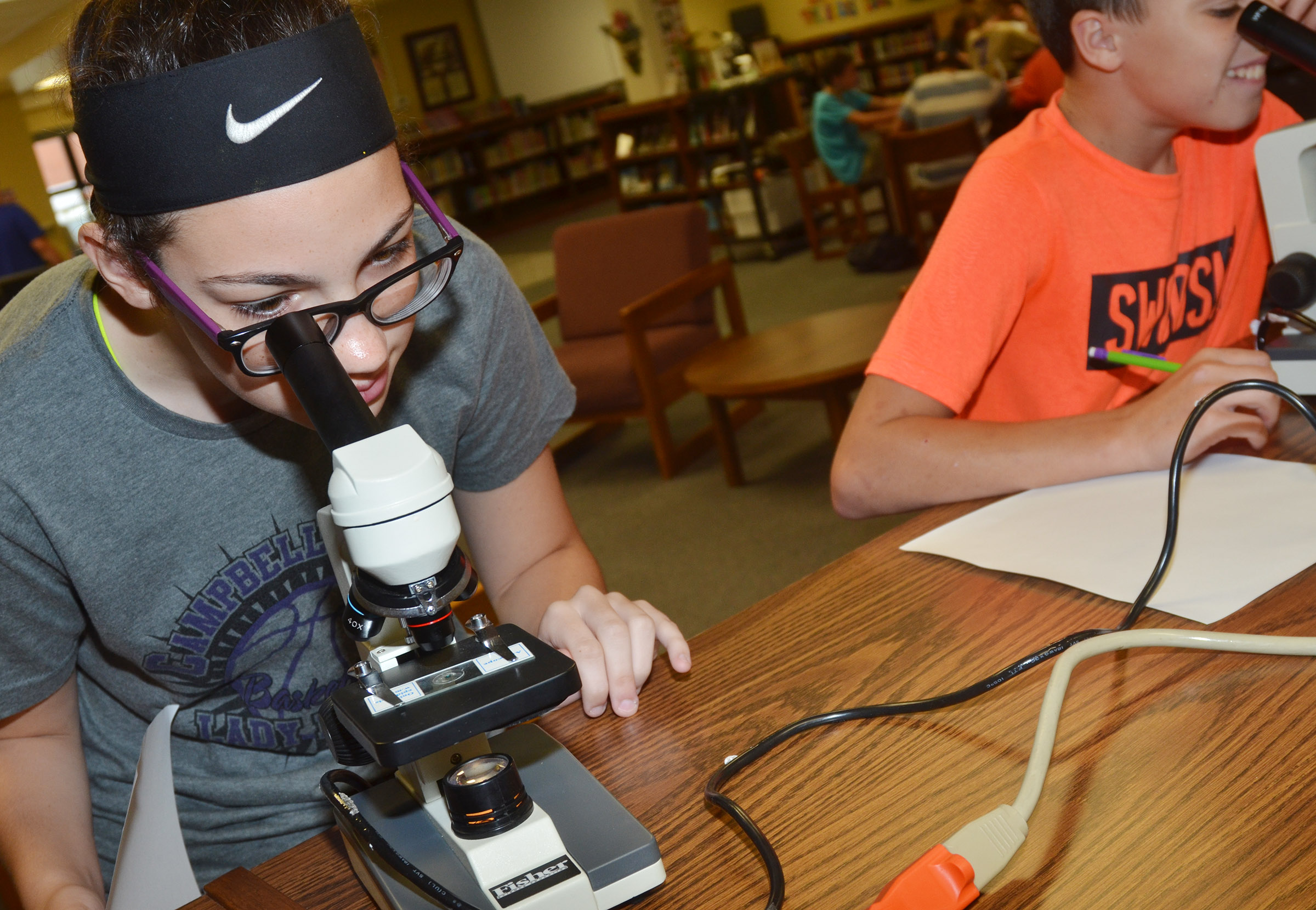 CMS seventh-grader Mary Russell looks at a piece of onion under a microscope.