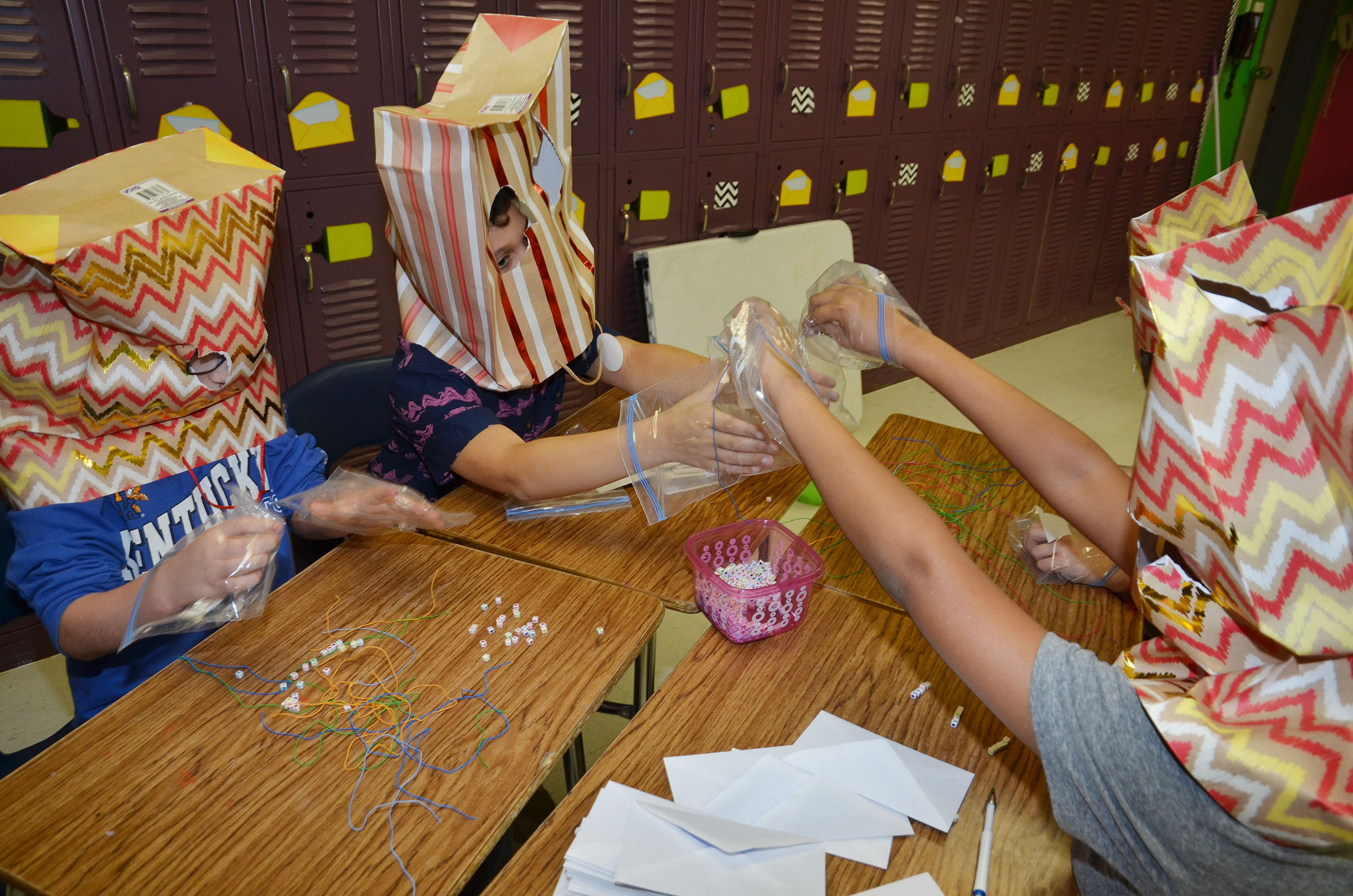 CMS sixth-graders make bracelets while wearing zip lock bags for gloves and bags as head gear.