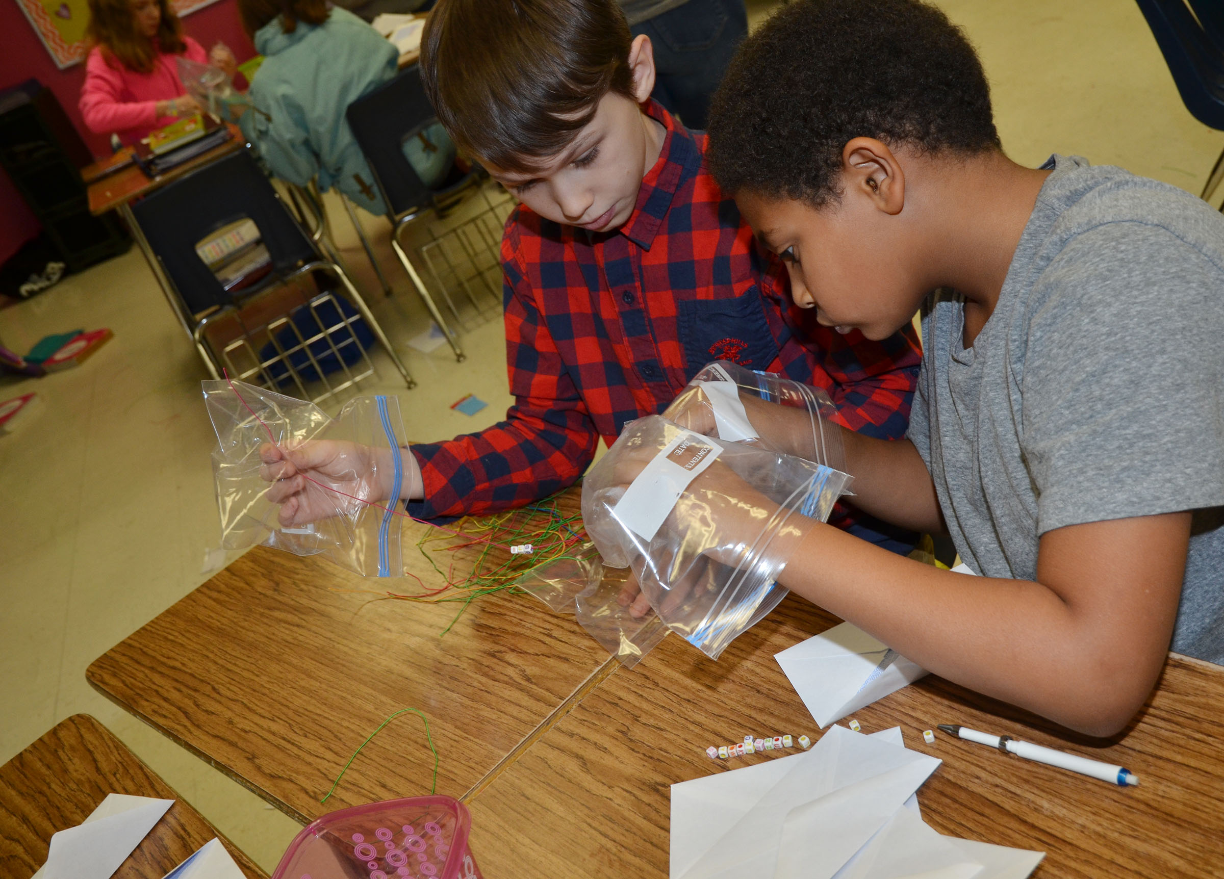 CMS sixth-grader Logan Wilson, at left, and Nasir Johnson make bracelets while wearing zip lock bags for gloves.