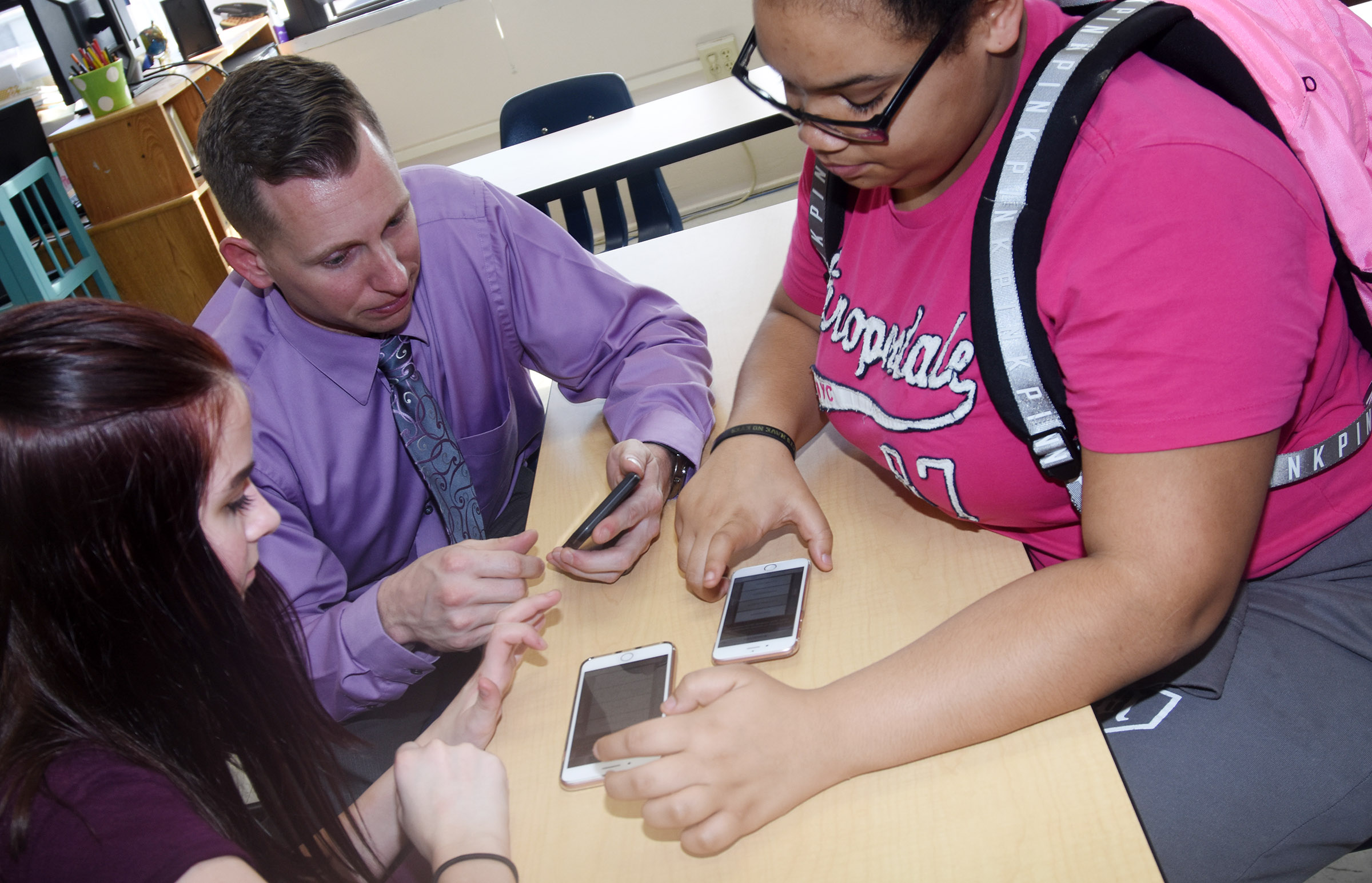 CMS Principal Zach Lewis works with eighth-graders Destiny Agee, at left, and Brae Washington as they compete in a trivia game.