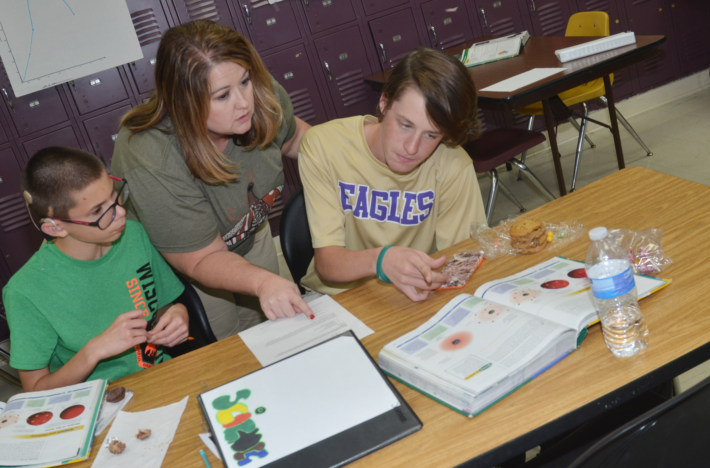 CMS science teacher Amy Knifley helps eighth-graders Grant Lawson, at left, and Seth Hash compare their candies to the atomic models.
