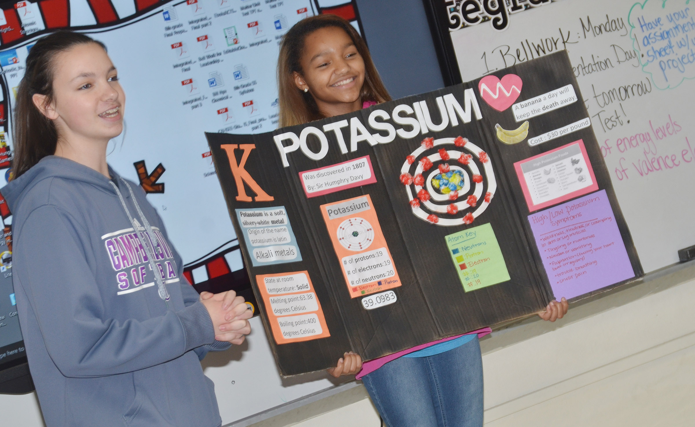 CMS eighth-grader Karley Morris, at left, presents about Potassium as classmate Alexis Thomas holds her poster.