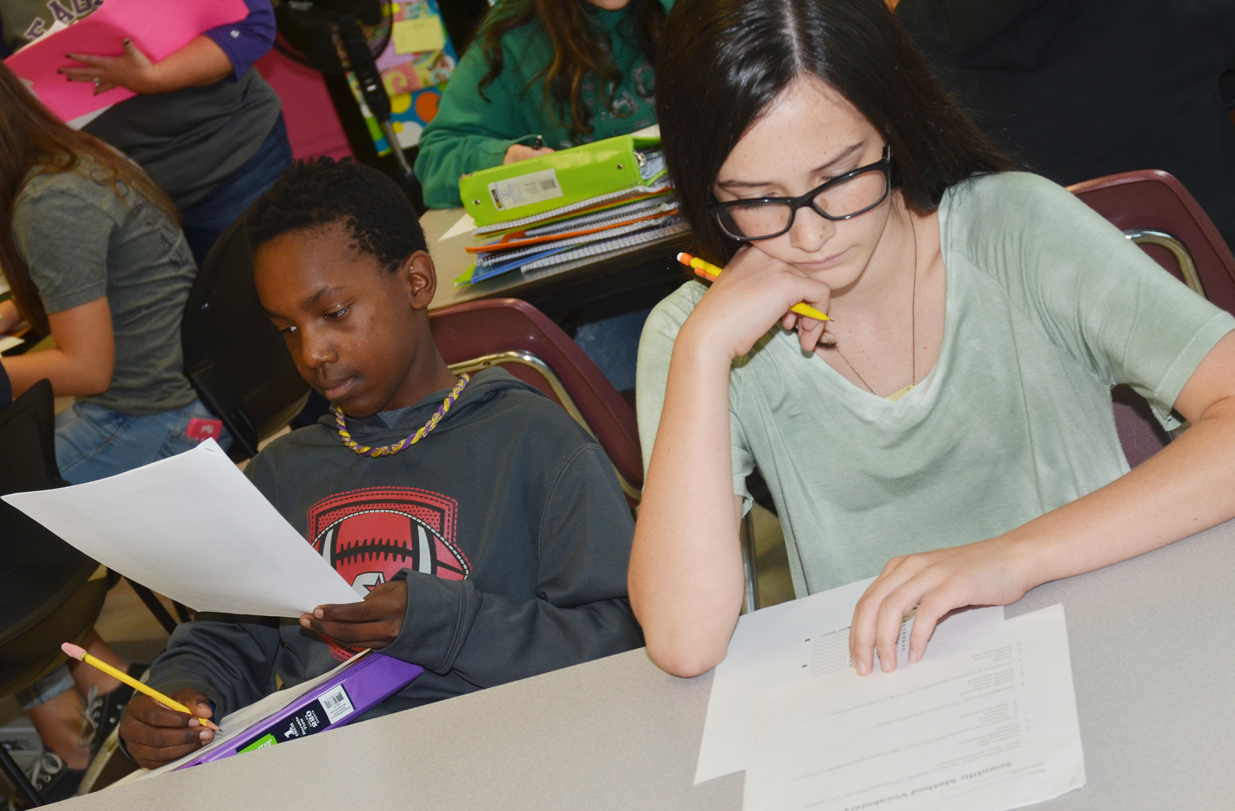 CMS eighth-graders Jadan Furman, at left, and Sarah Adkins answer the questions on their vocabulary quiz.