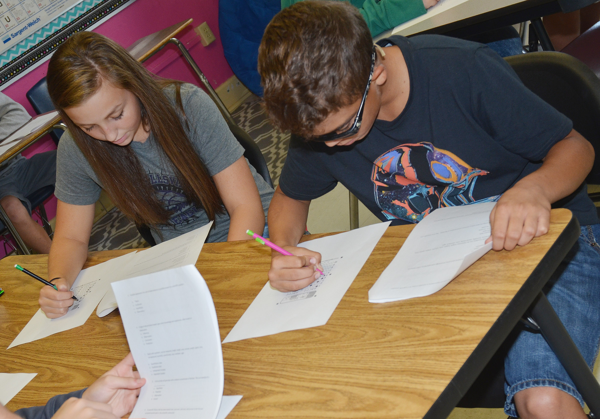 CMS eighth-graders Lainey Watson, at left, and Logan Phillips answer the questions on their vocabulary quizzes.