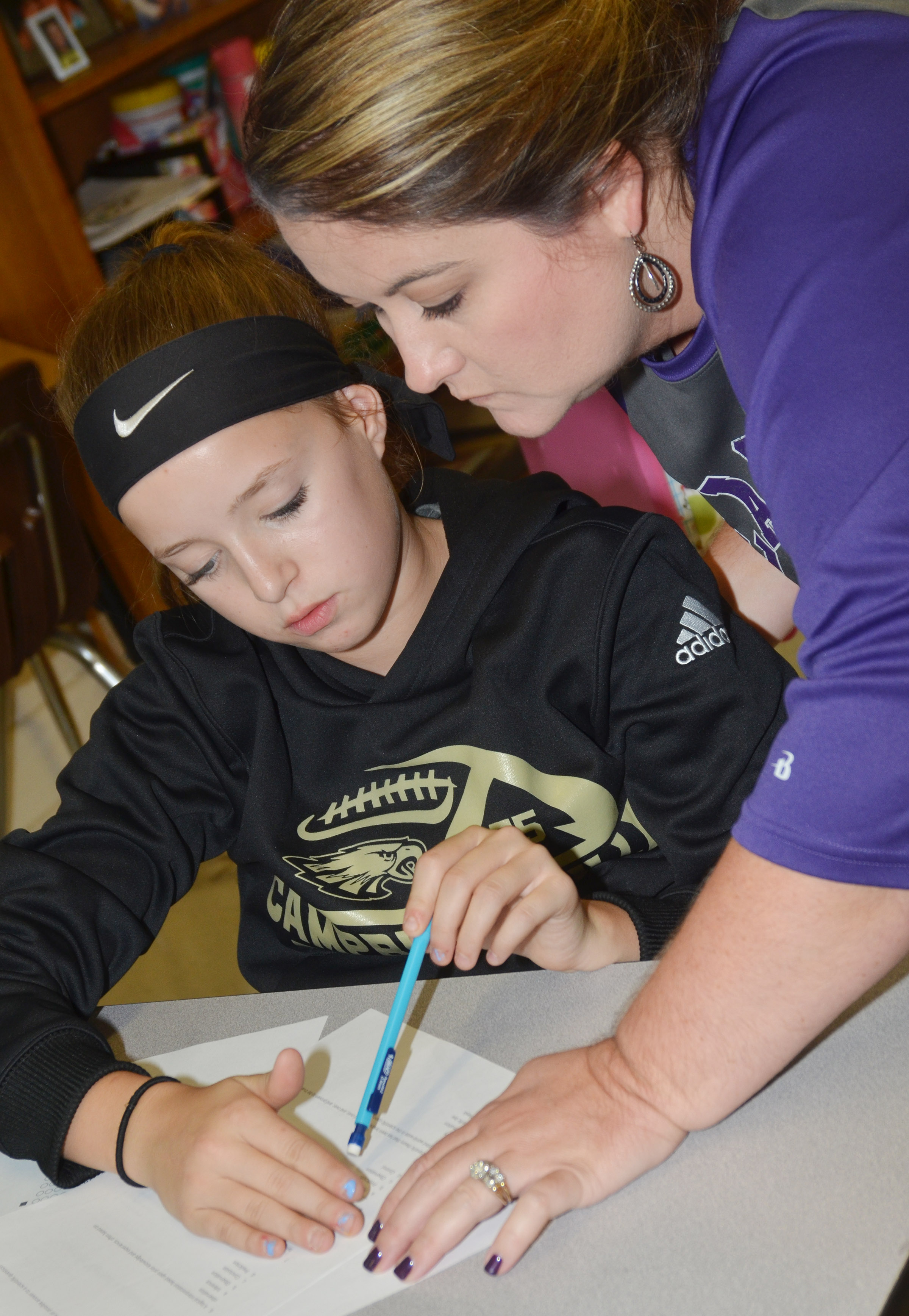 CMS eighth-grade teacher Amy Knifley helps Rylee Petett with her vocabulary quiz