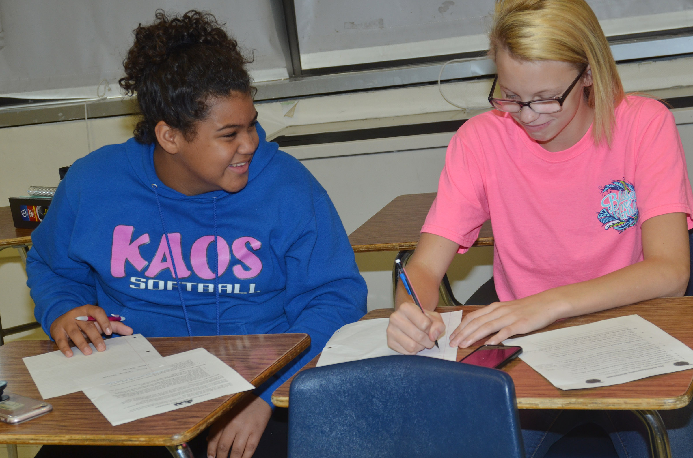CMS seventh-graders Asia Barbour, at left, and Jade Wheeler work on their autobiographical assignment.