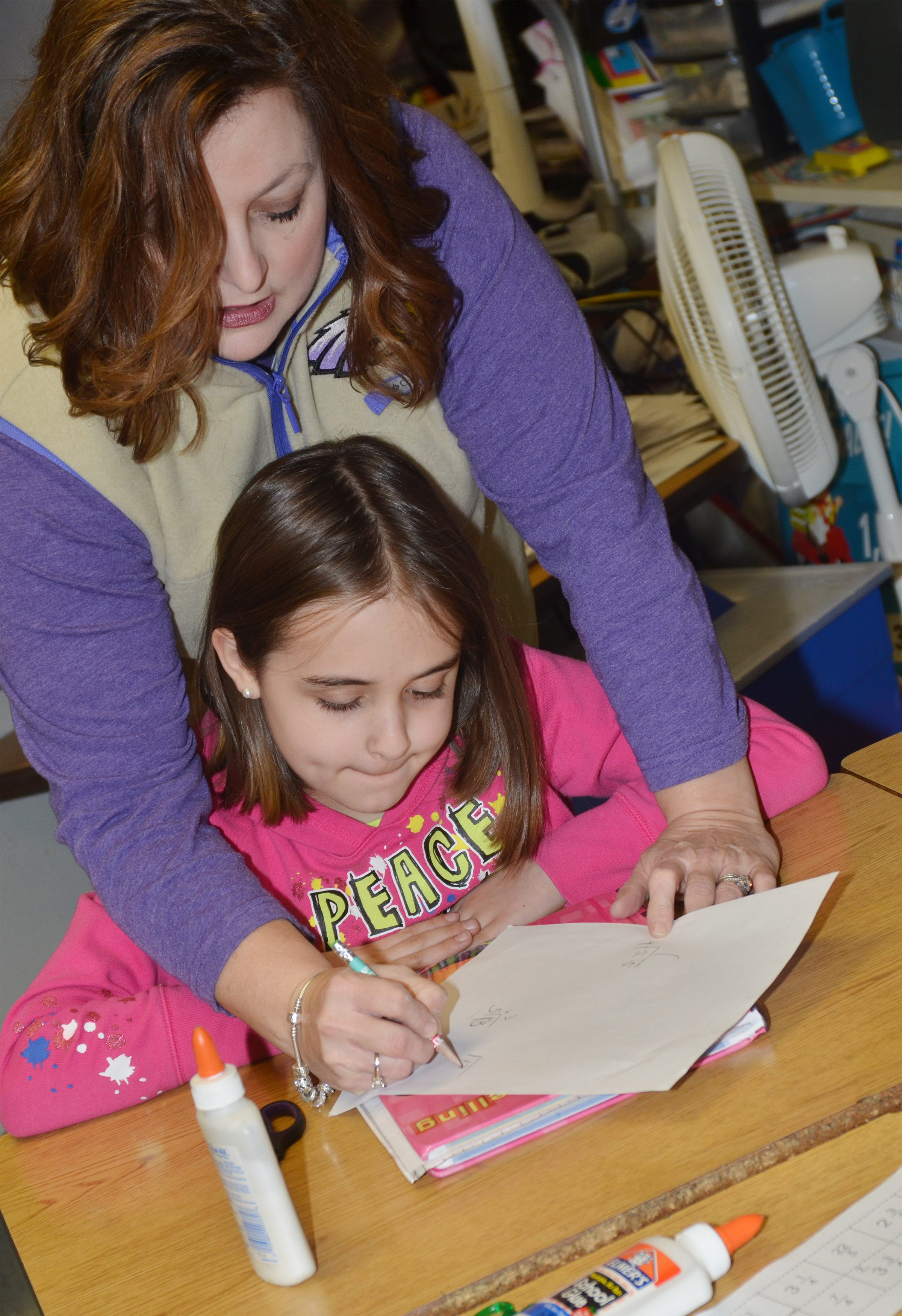 CMS fifth-grade teacher Garnetta Murrell helps Anna Floyd add fractions.